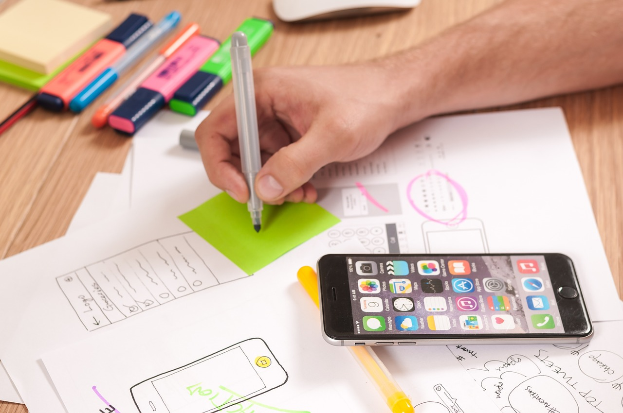 Someone designing app features on paper with pens and markers.