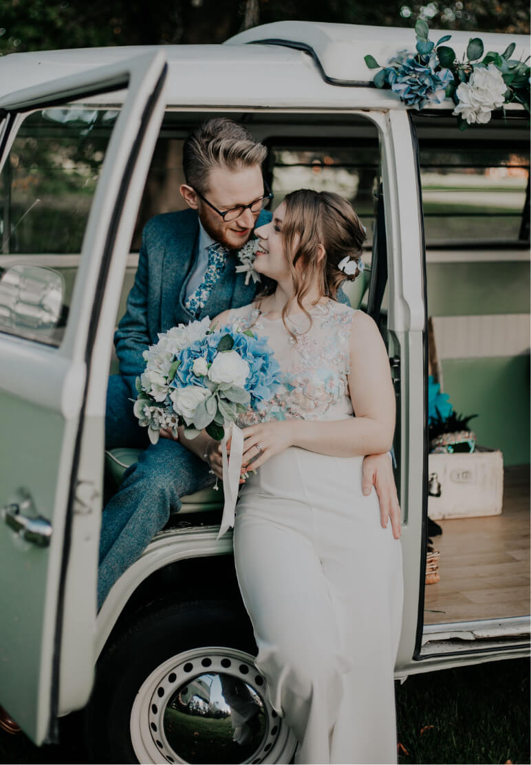 A couple in front of a VW camper van on their wedding day.