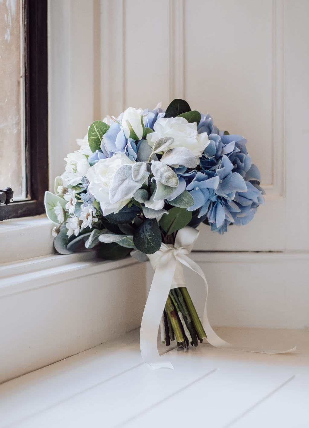 A beautiful blue and white wedding bouquet leaning against a window sill.