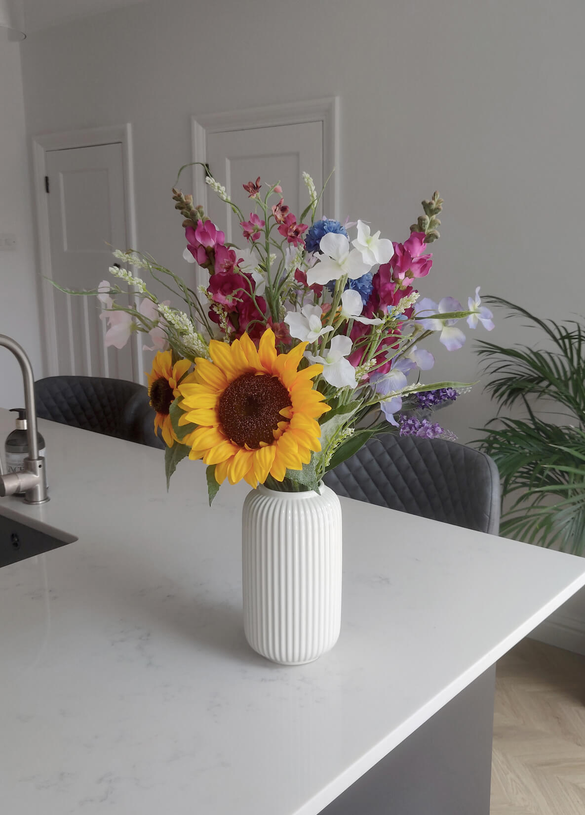 A bouquet of brightly coloured flowers including sunflowers, in a vase in the kitchen.