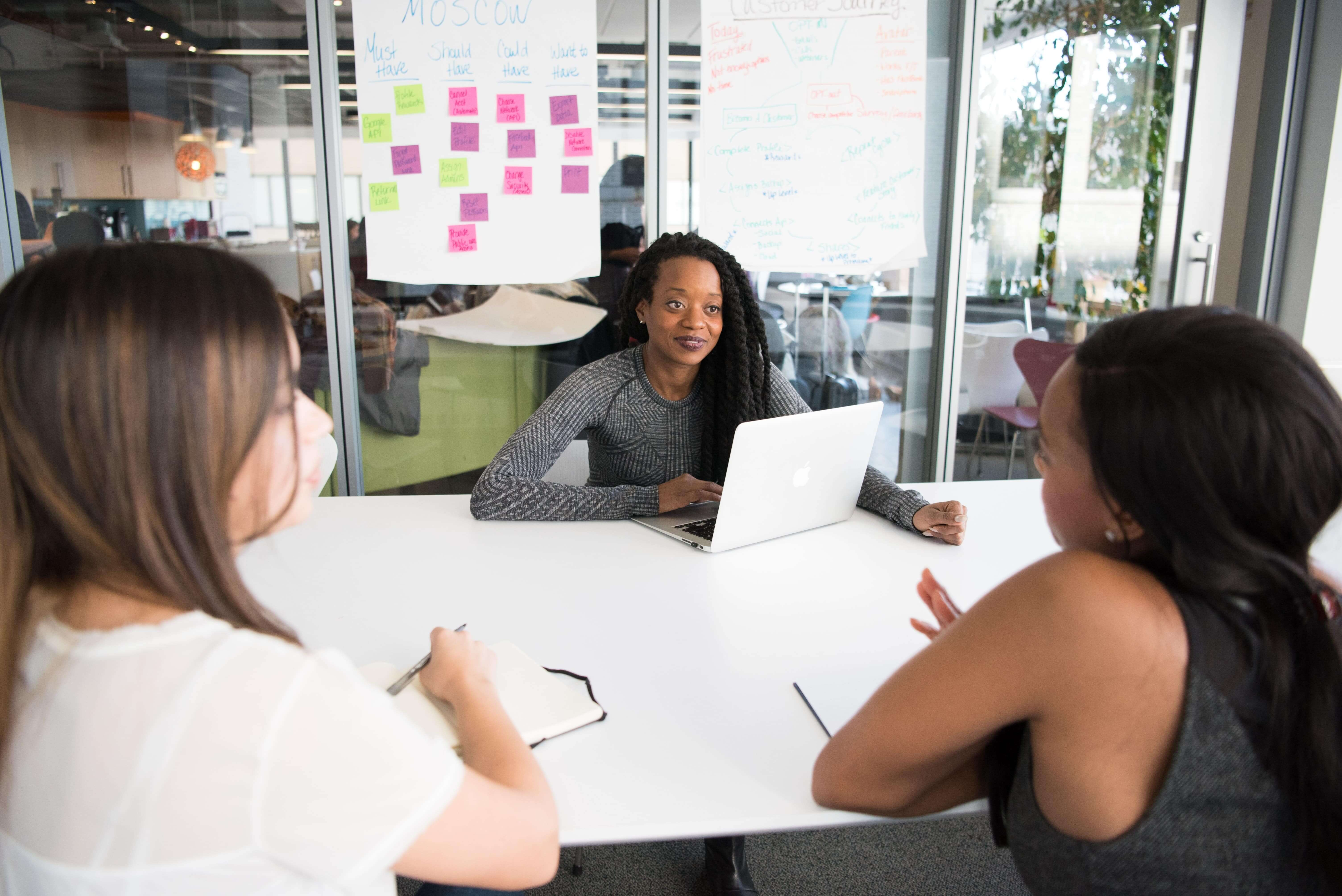 Three woman entrepreneurs discussing, learning, educating, and supporting each other as founders