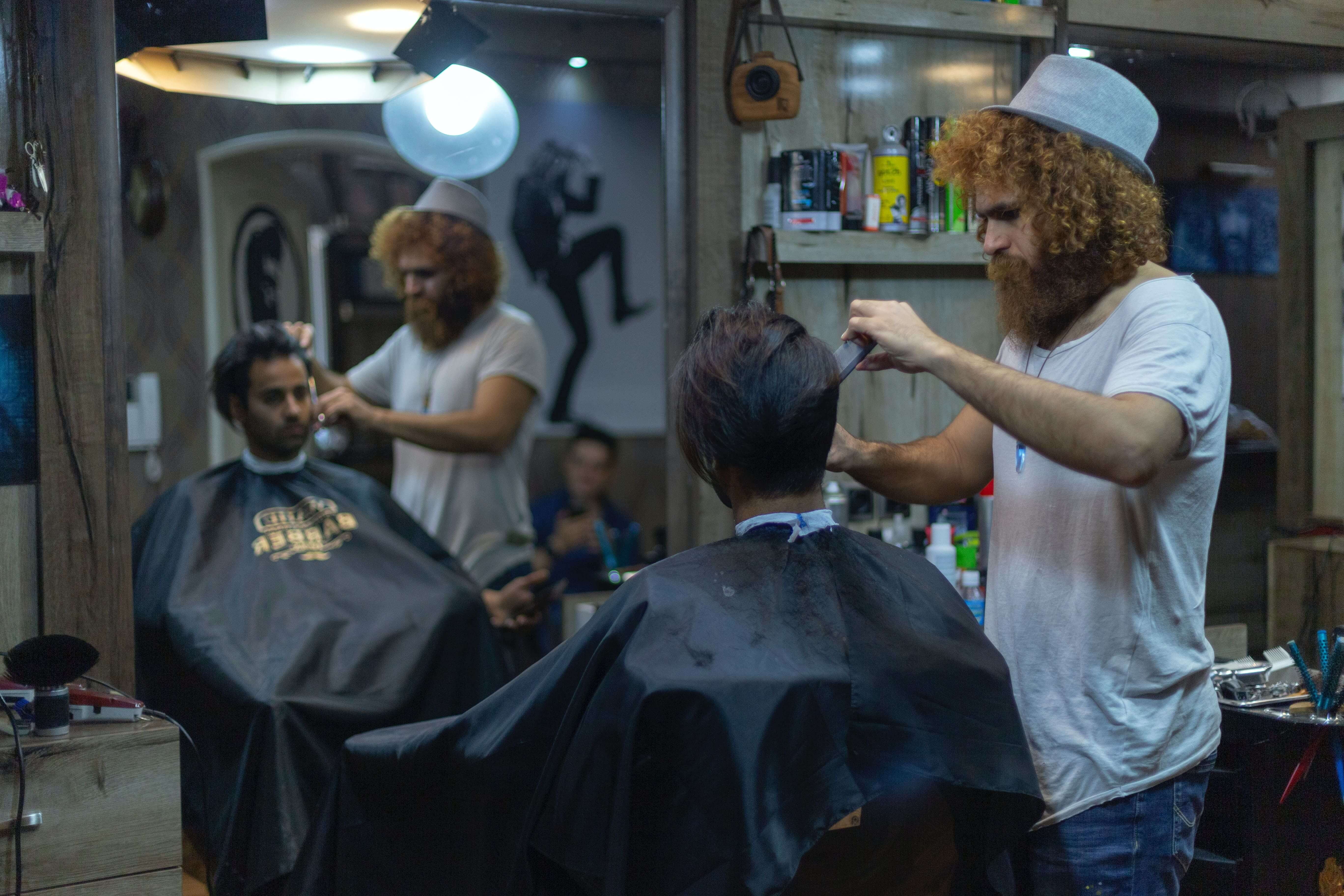 A small business hair salon owner entrepreneur caring for his customer