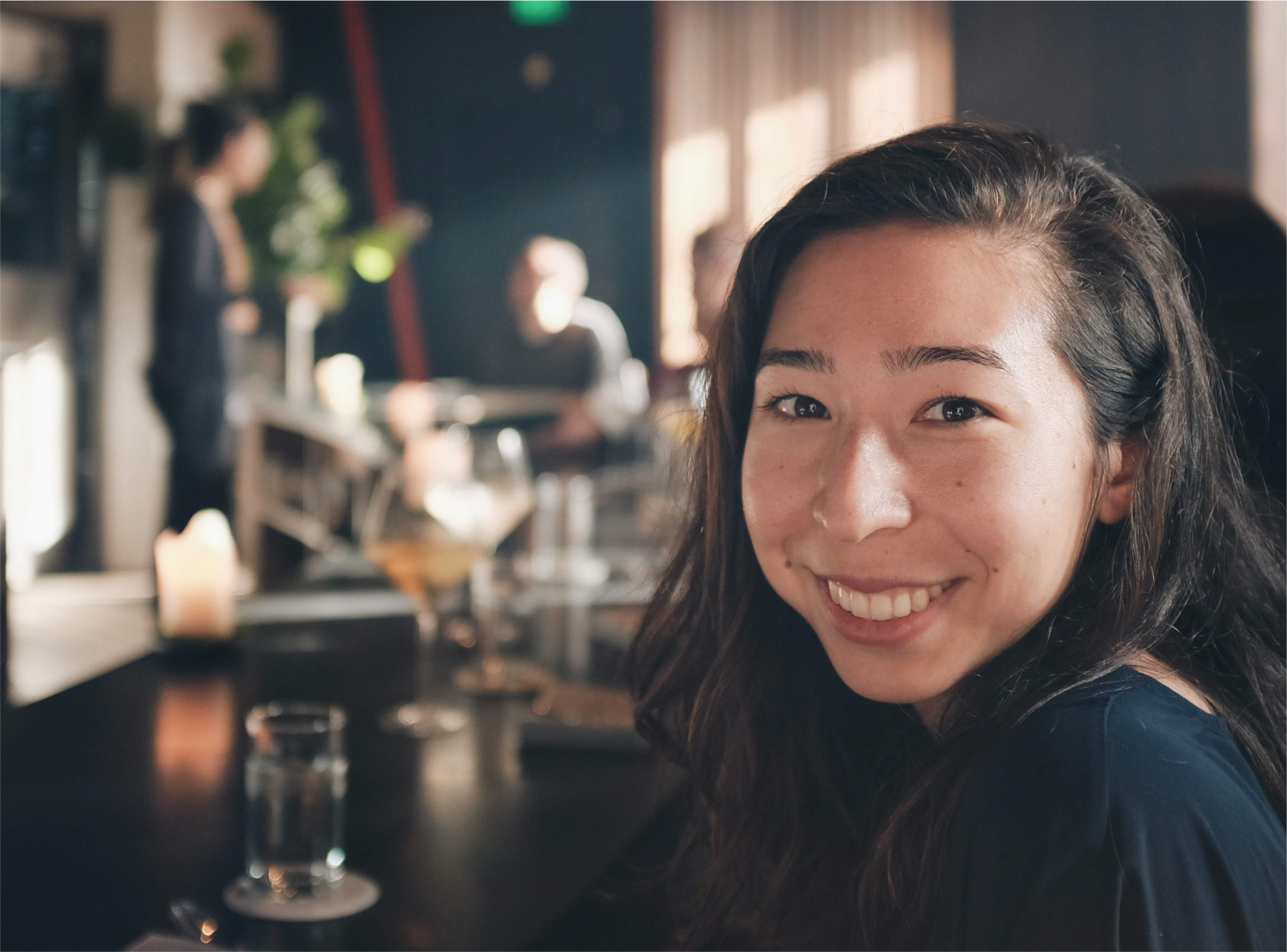 A photo of the site author, Sara, seated at a restaurant and smiling at the camera.