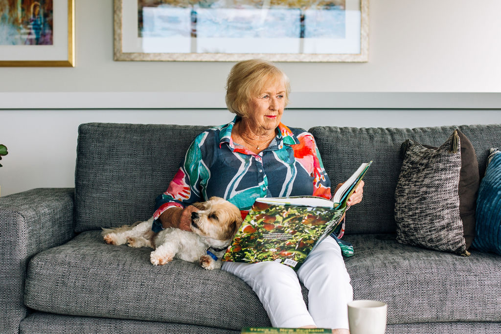 Woman reading a book on the couch with her dog