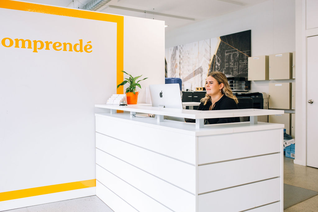 Receptionist sitting at front desk in Comprende office space.