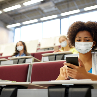 A girl holding a phone in a classroom wearing a protective mask