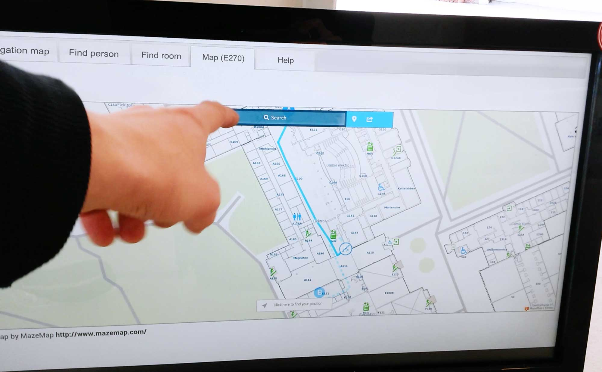 Hand touching a large info screen with MazeMap on it
