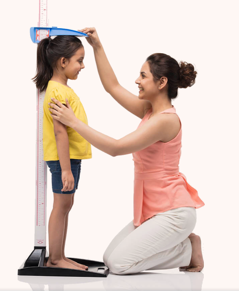 mother measuring her daughters heigh growth