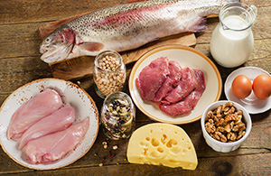 various food items on a table: chicken breast, salmon, milk, nuts, eggs, cheese
