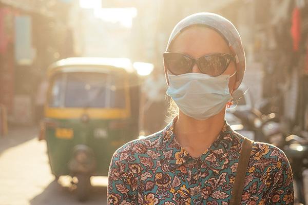 Woman in Asian street scenery, wearing face mask