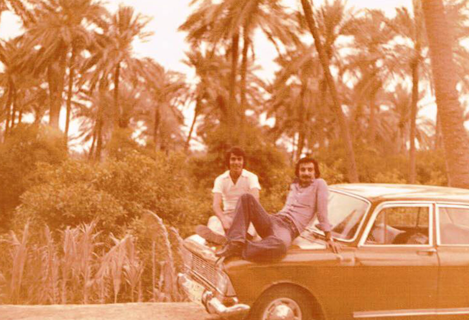 An image of two men sitting on the hood of a car with palm trees behind them in 1978 as submitted to the Iraq Photo Archive.