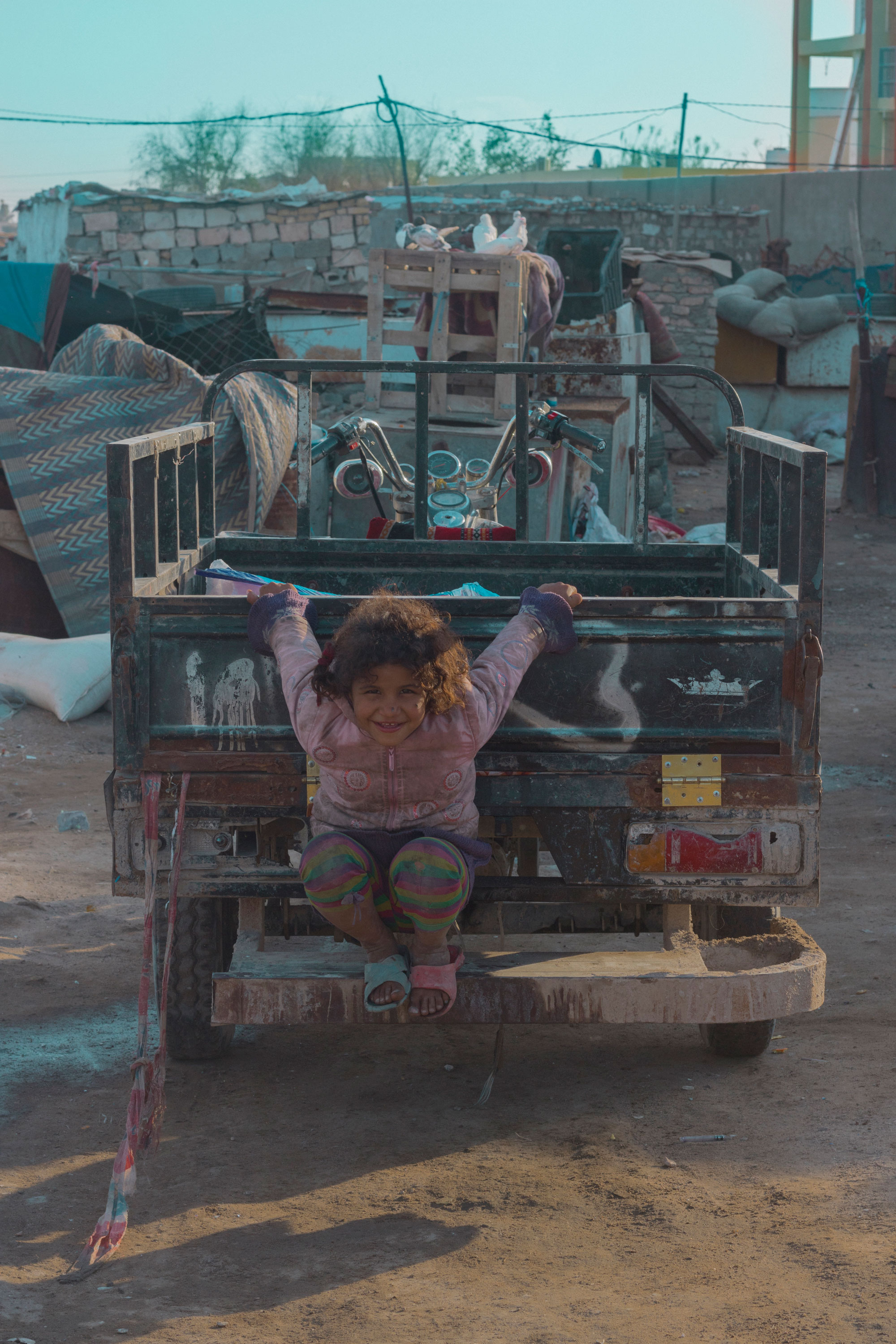 A child looks into the camera as she hangs on to the back of a stationary pick up truck.