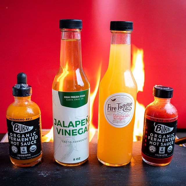 H&H Vinegars with Burn Hot Sauce and Fire Tongue Vinegar sitting in front of fire