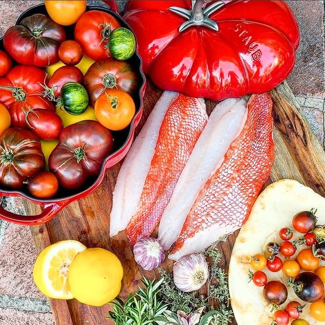 rockfish on cutting board with lemon, tomatoes. and other produce