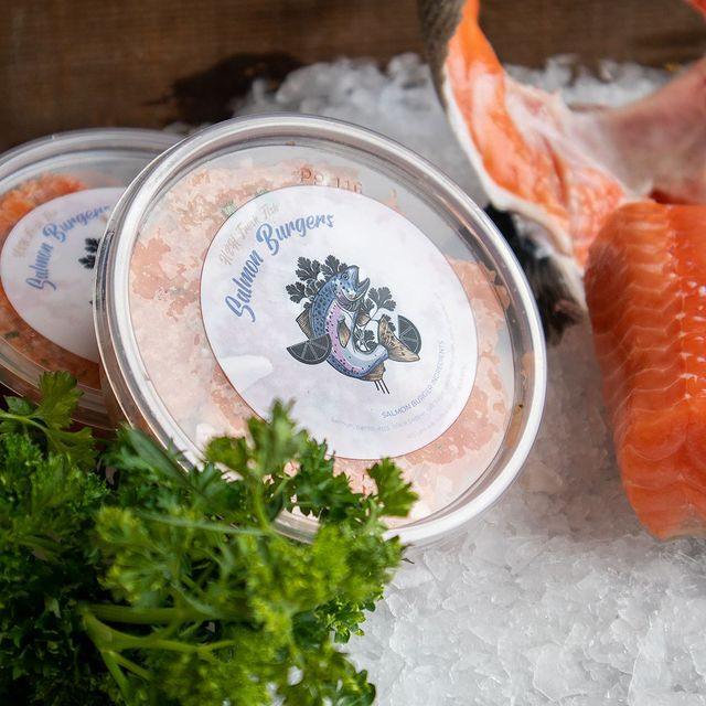 Salmon Burger next to Salmon Collars and Fillet on ice