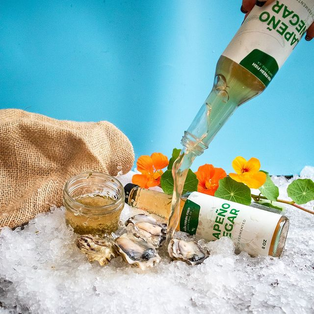 Jalapeño vinegar being poured on fresh oysters