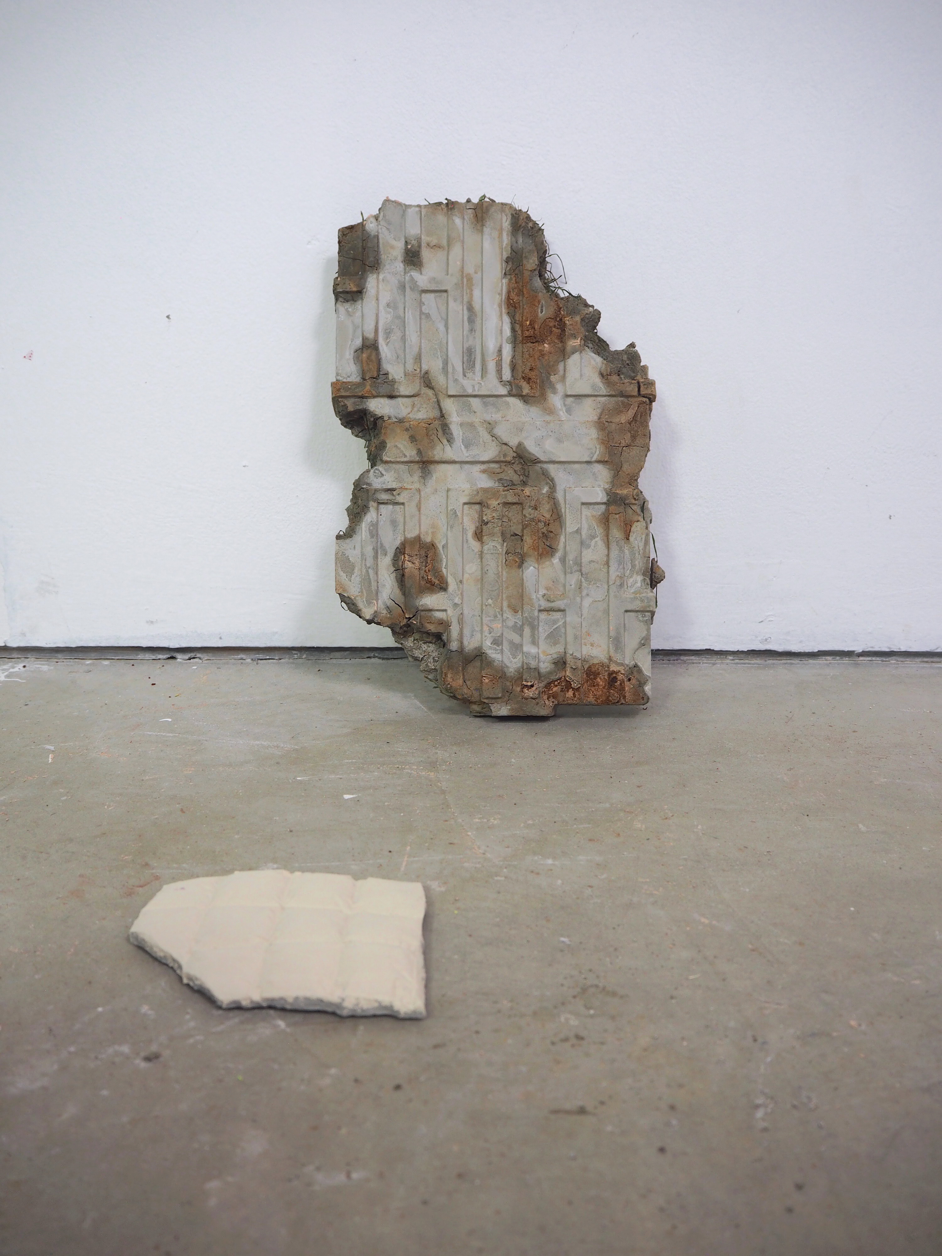 brown and grey sculpture on floor infant of white wall