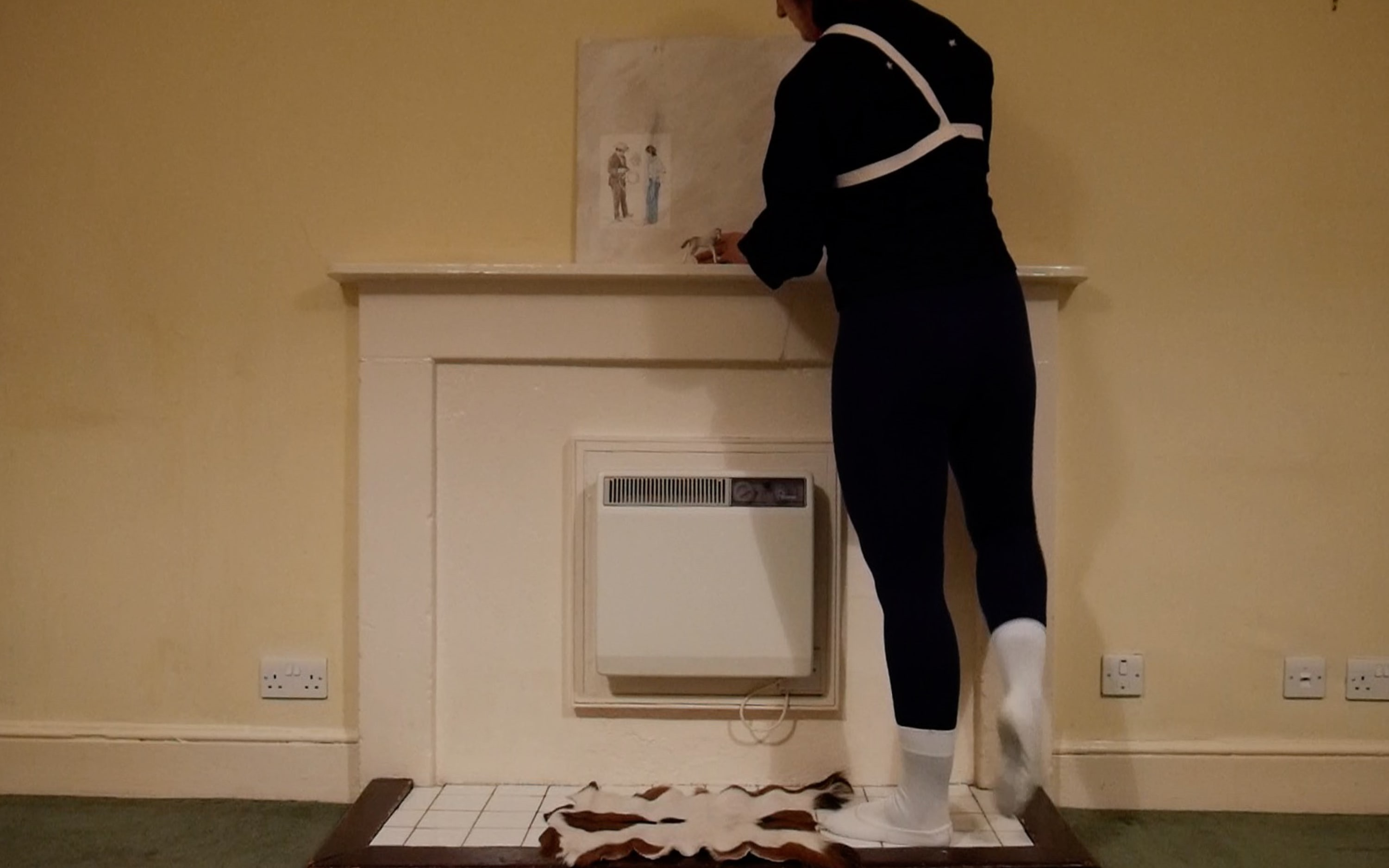 a man dressed in naval uniform and ballet shoes putting a painting of two men on to a mantlepiece.