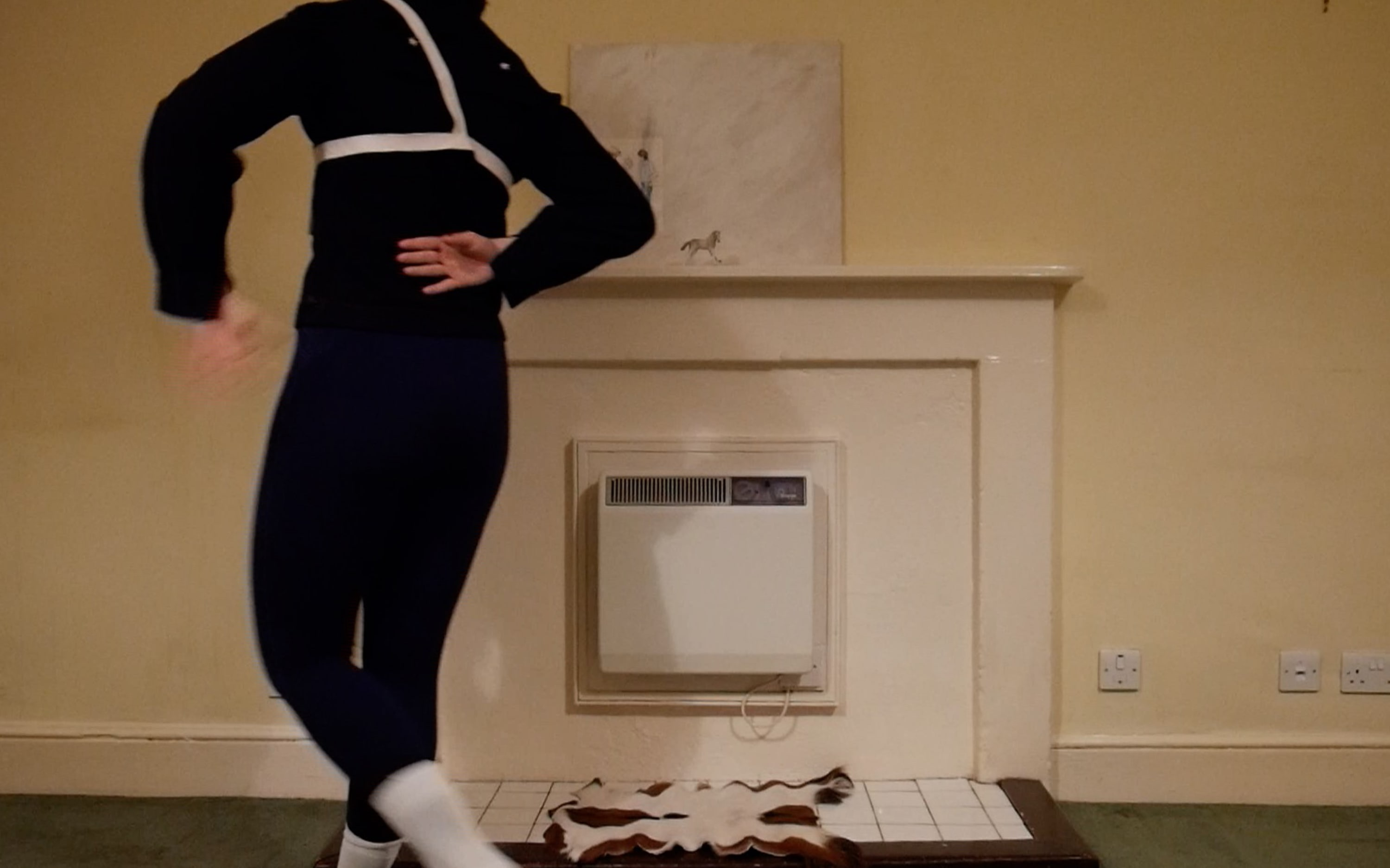 a man dressed in naval uniform and ballet shoes dancing around a painting of two men, which sits on a mantlepiece.