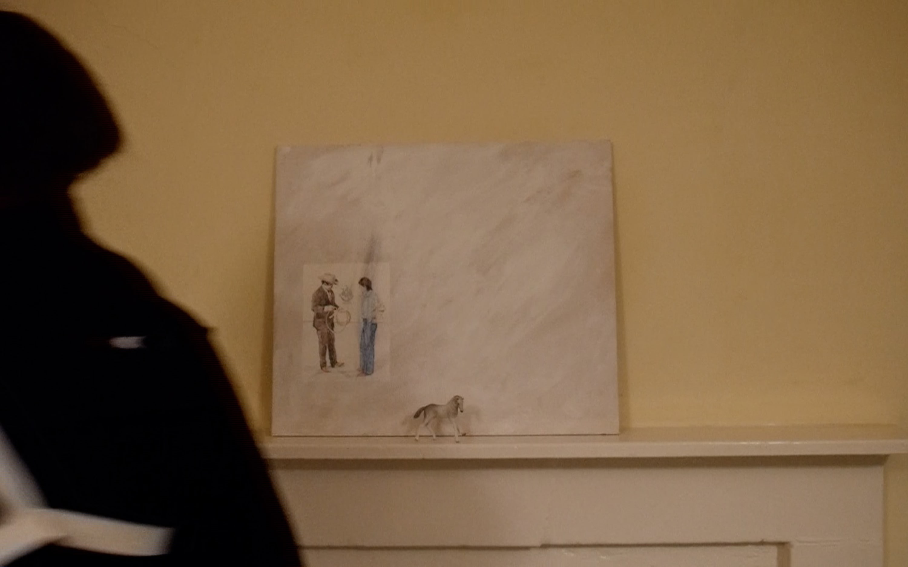 In front of the painting on the mantlepiece is a small figurine of a white foal with a bent leg. 2 men are in the painting.