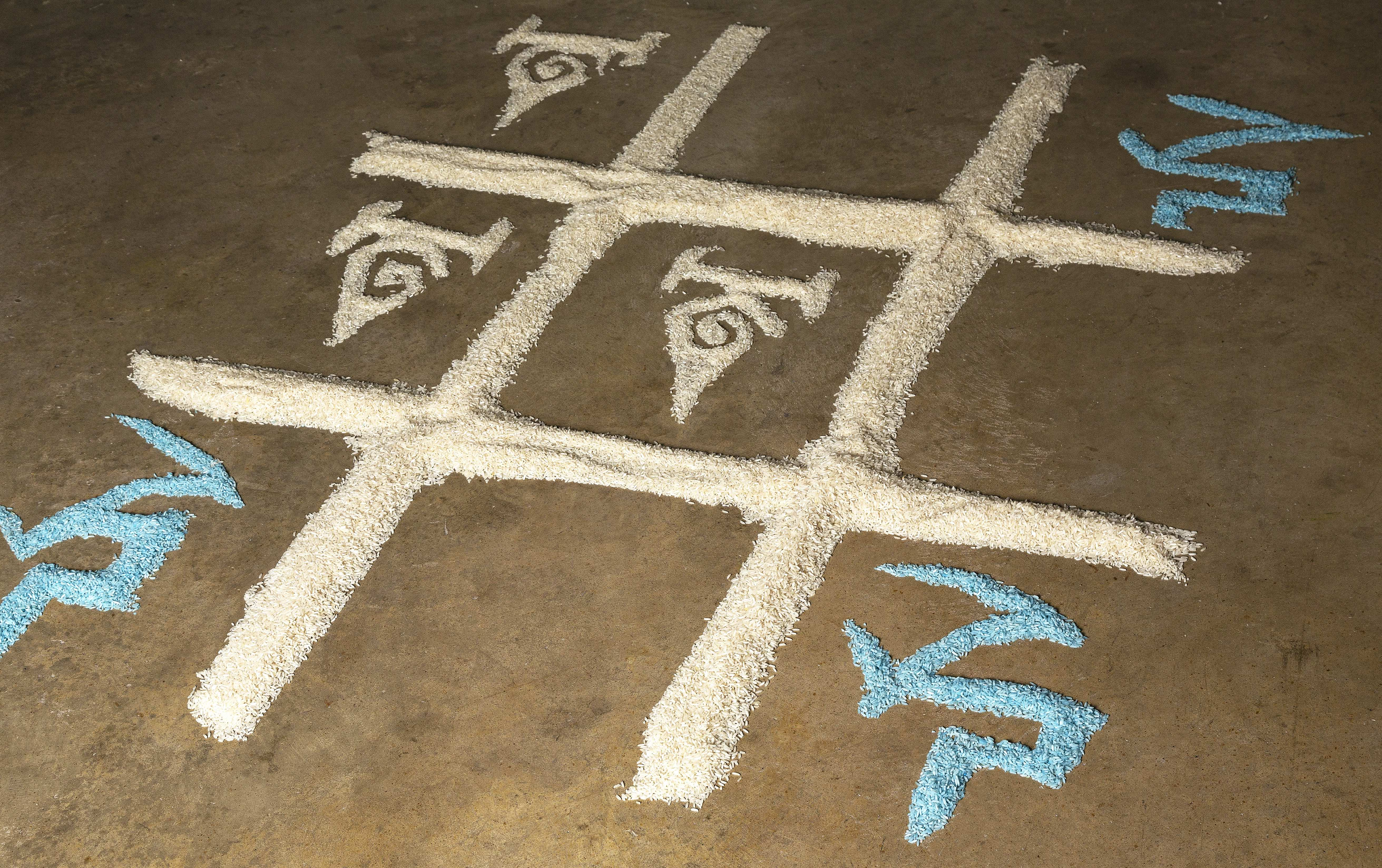 Blue dyed and un-dyed Basmati rice displayed on the floor in a noughts and crosses formation in an unrecognisable language.