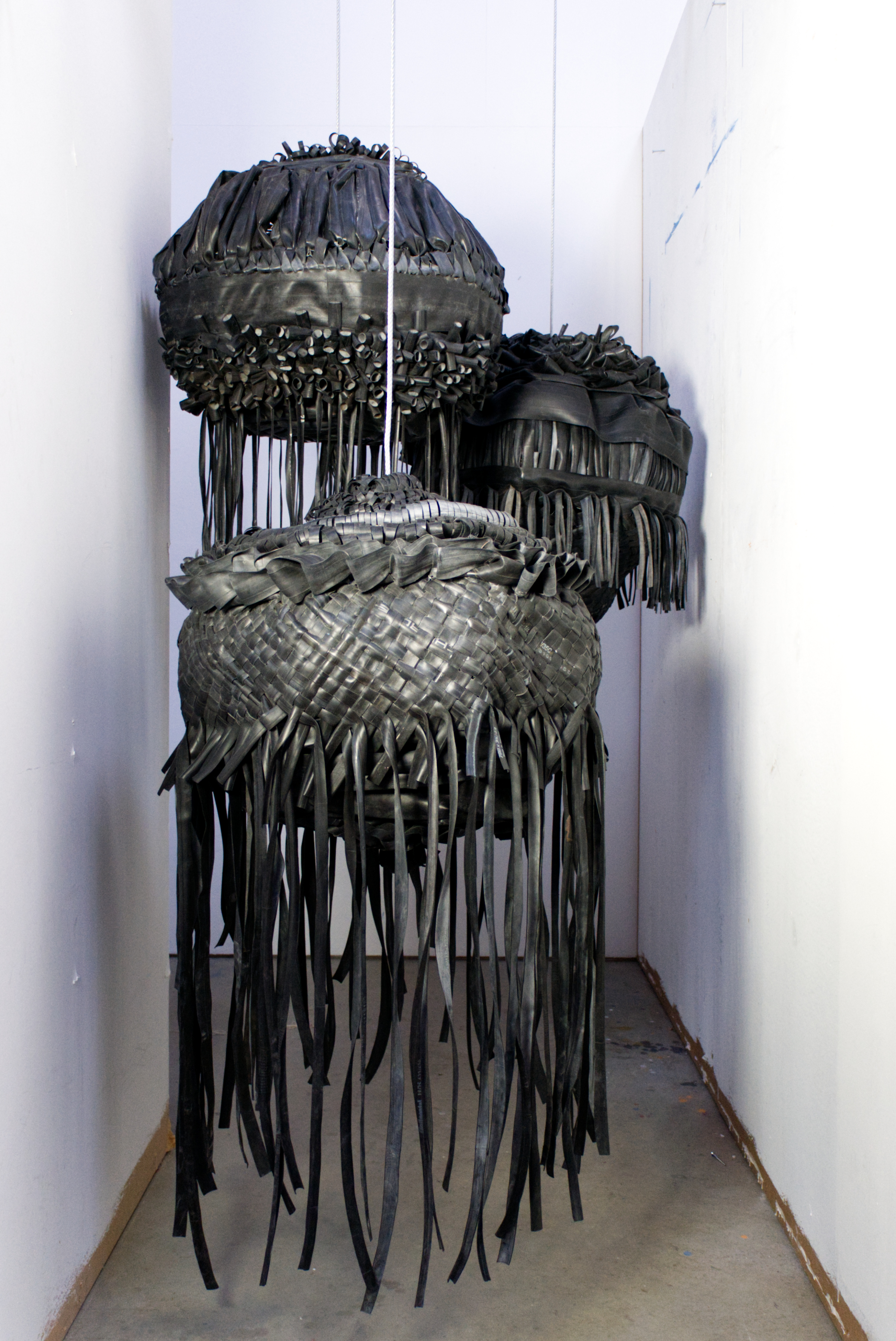 Suspended at different heights from metal wire, three sculptures made of black rubber are installed in a narrow corridor. The sculptures are black and highly textured from a variety of weaving, platting and knotting techniques. The light reflects from the smooth black rubber to inherence the textures. the three sculptures all have rubber tassels hanging from them.