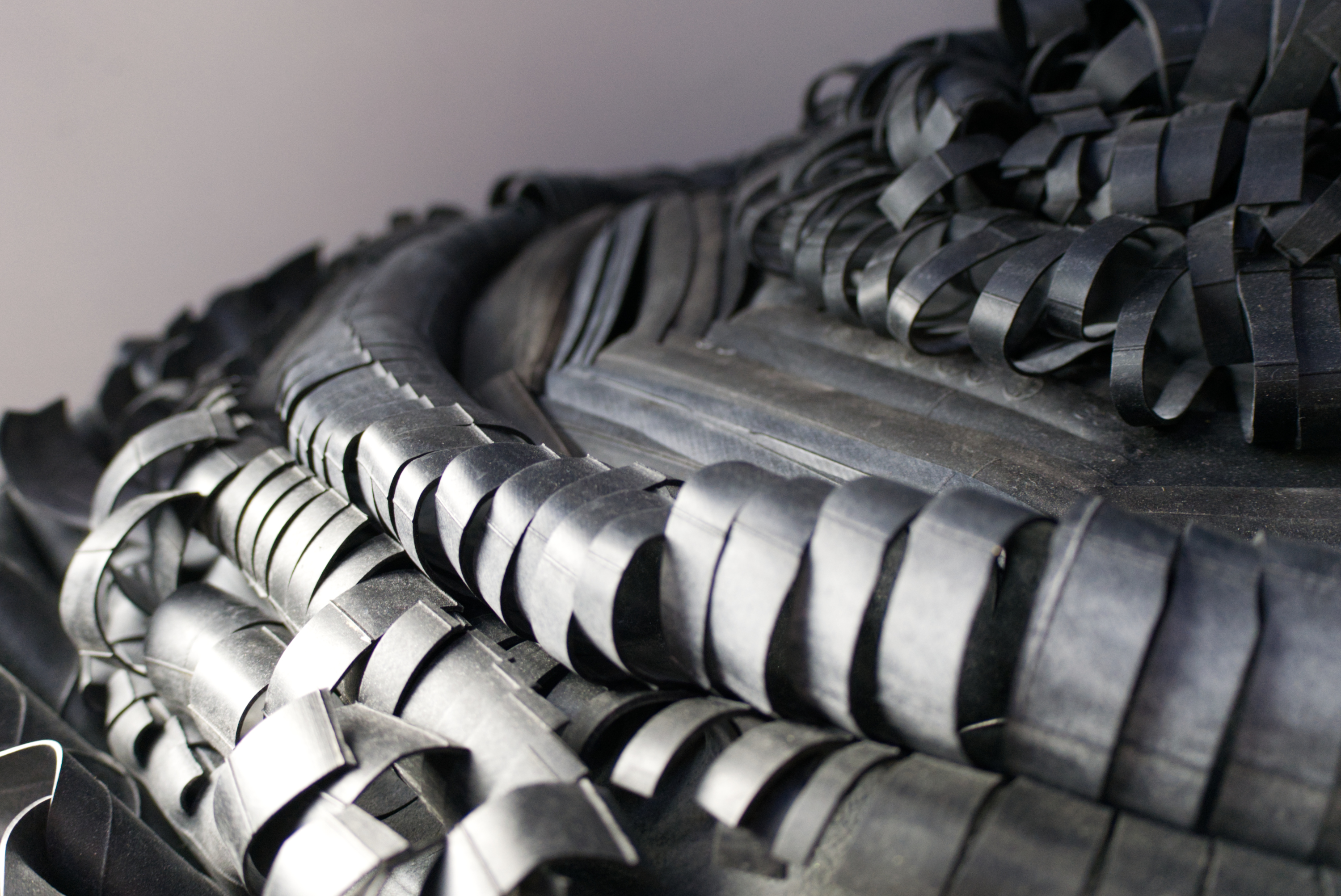 A detail of a suspended rubber woven sculpture. The rubber creates a varied layered textures over the curve of the sculpture.
