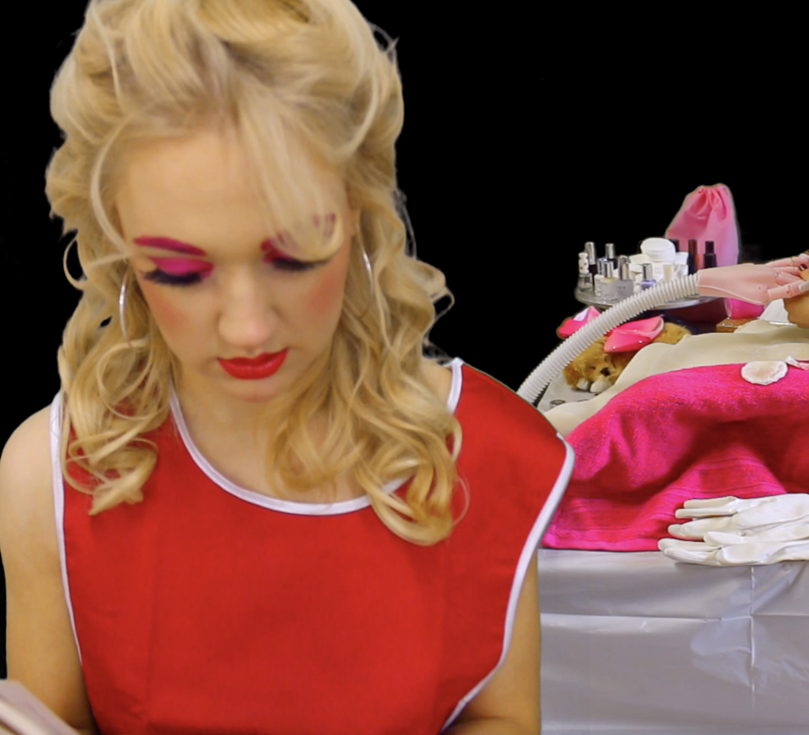 blonde girl dressed in a beautician's uniform reads from Kawabata's short story 'One Arm', while the same girl paints the nails of a mechanical arm.