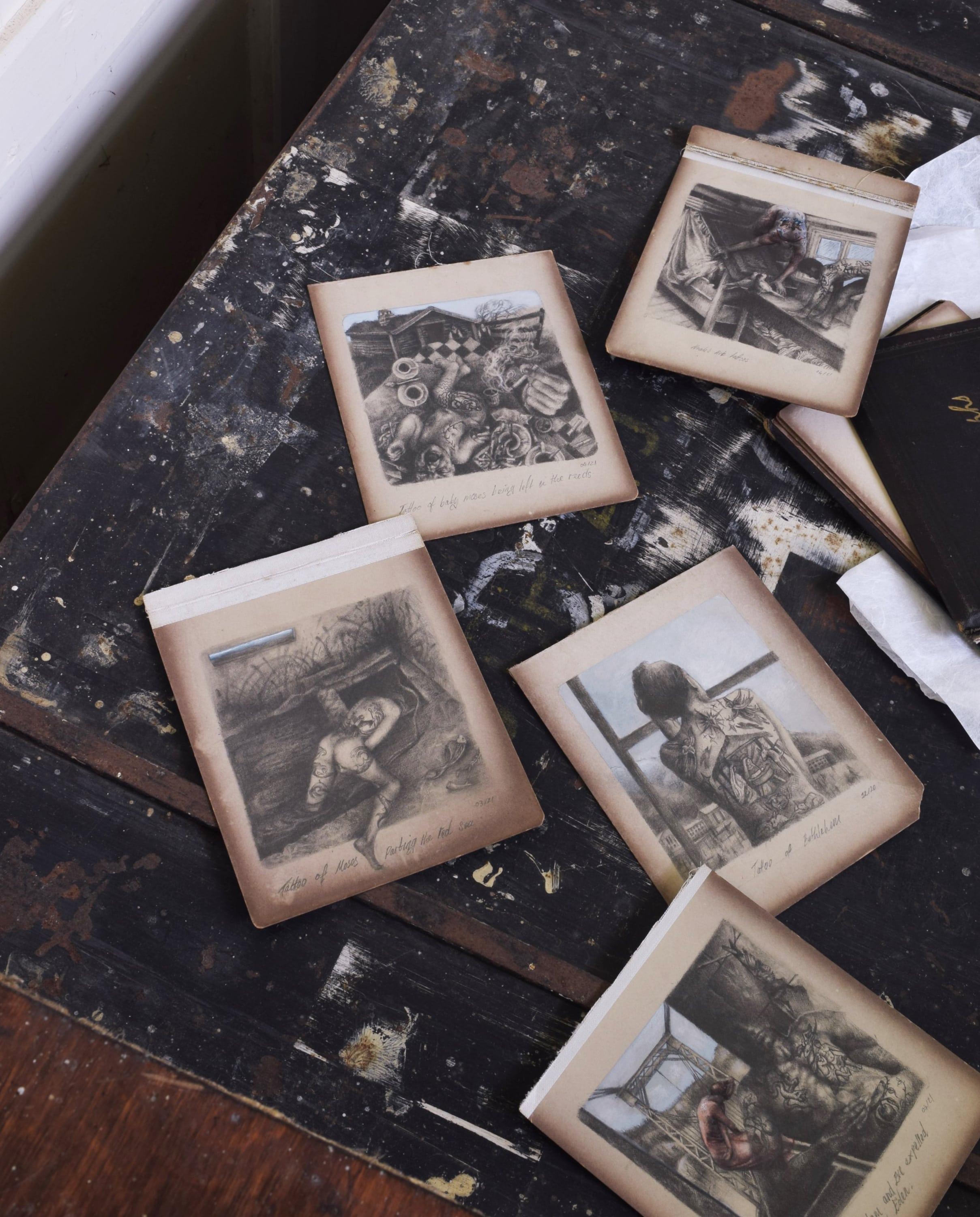 A series of five small drawings and an old photo album are scattered across a trunk, in the back room of a church.