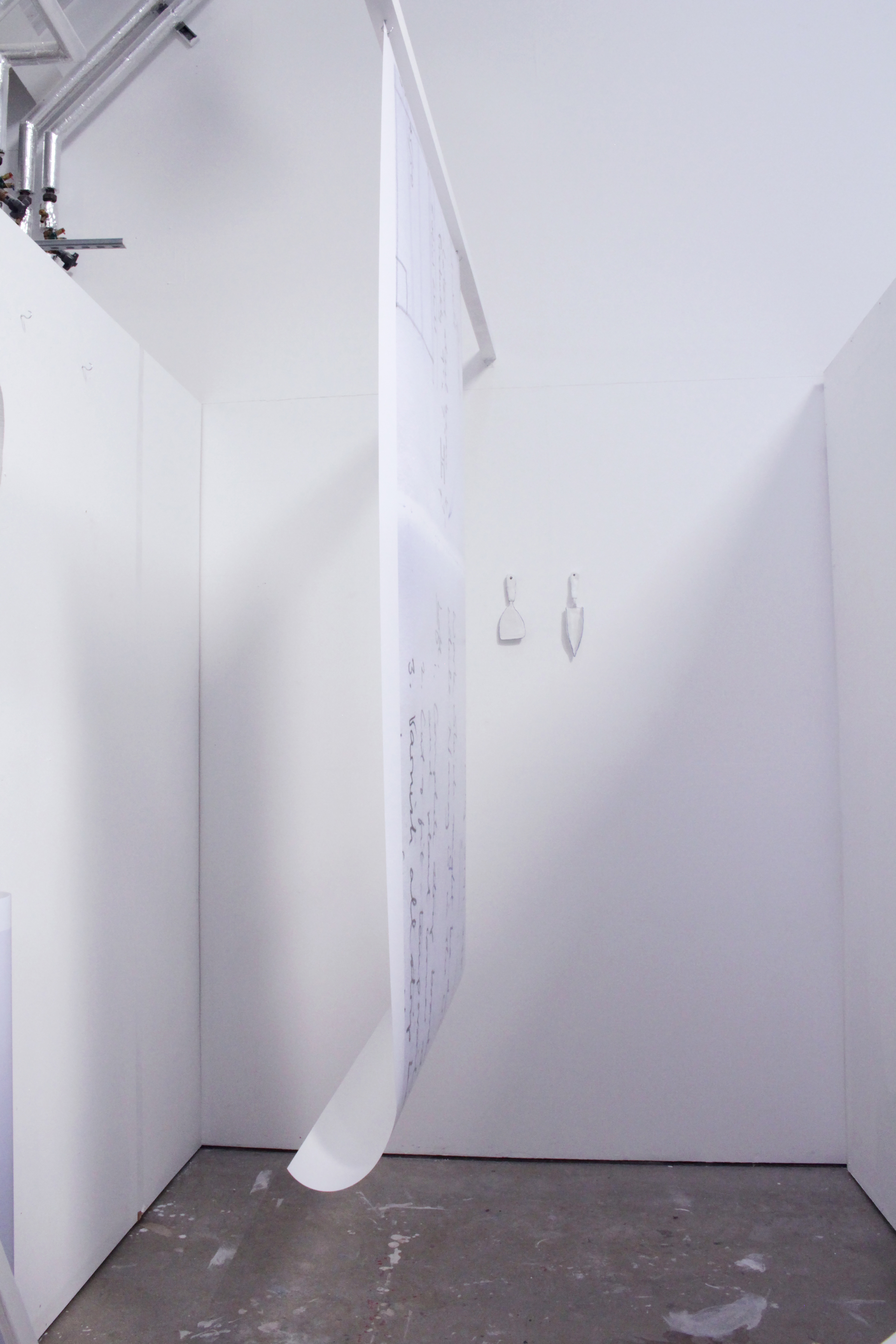 The video depicts a portrait view of an enlarged to do list about 1 metre in width and 2 metres in length hanging from a bar raised around 7 foot from the floor in the middle of a small rectangular studio space. The room is empty and blank. The scroll mimics a length of wallpaper.