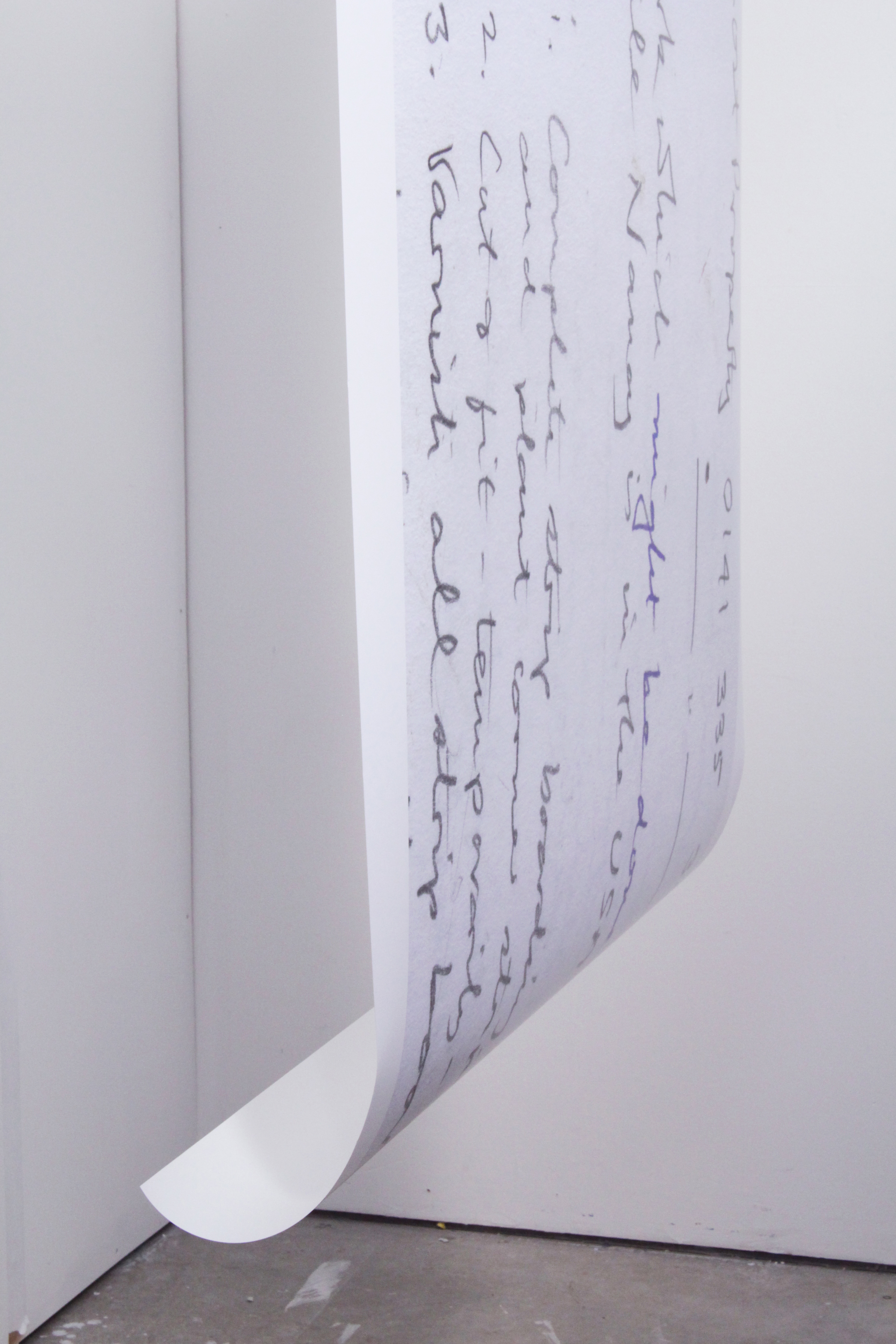 The image depicts a close up view of an enlarged to do list about 1 metre in width and 2 metres in length hanging from a bar raised about 7 foot from the floor in the middle of a small rectangular studio space. The room is empty and blank.