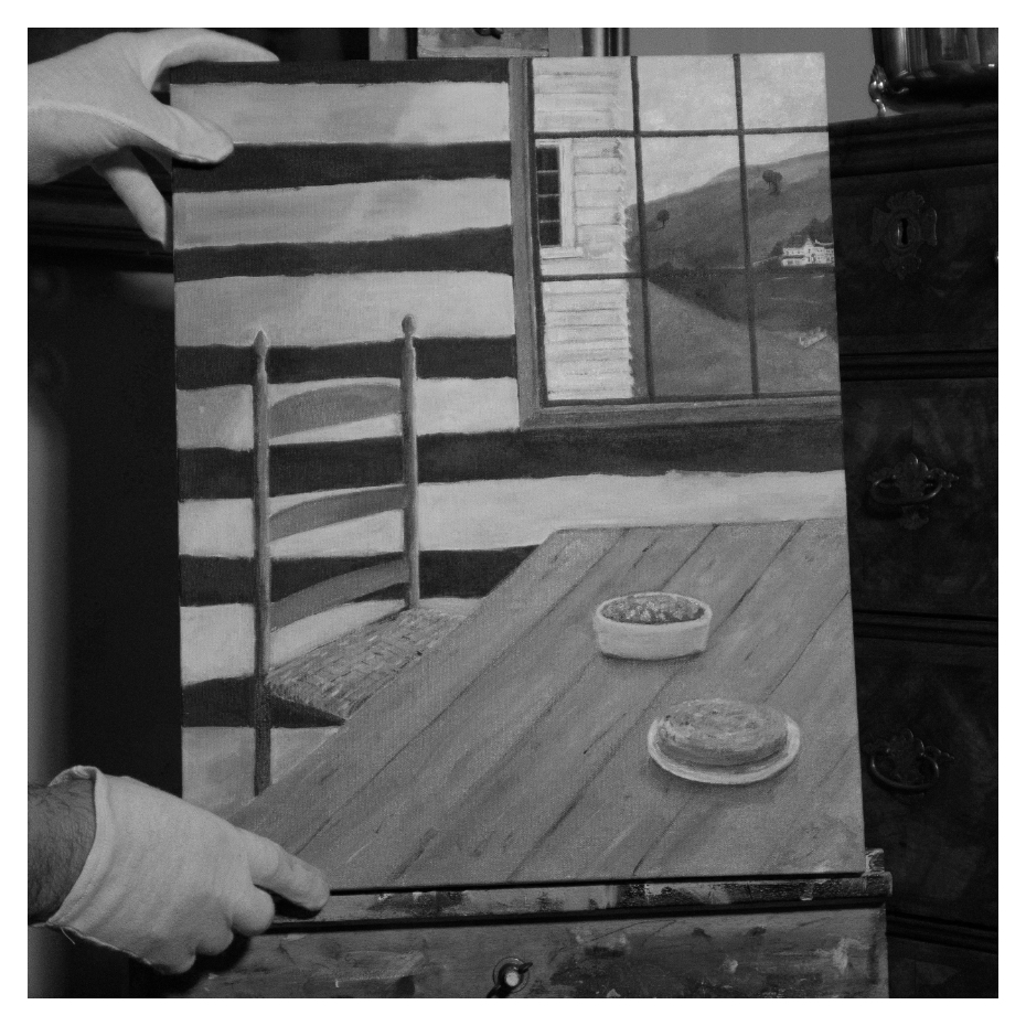 Gloved hands holding painting of a landscape and house in black and white