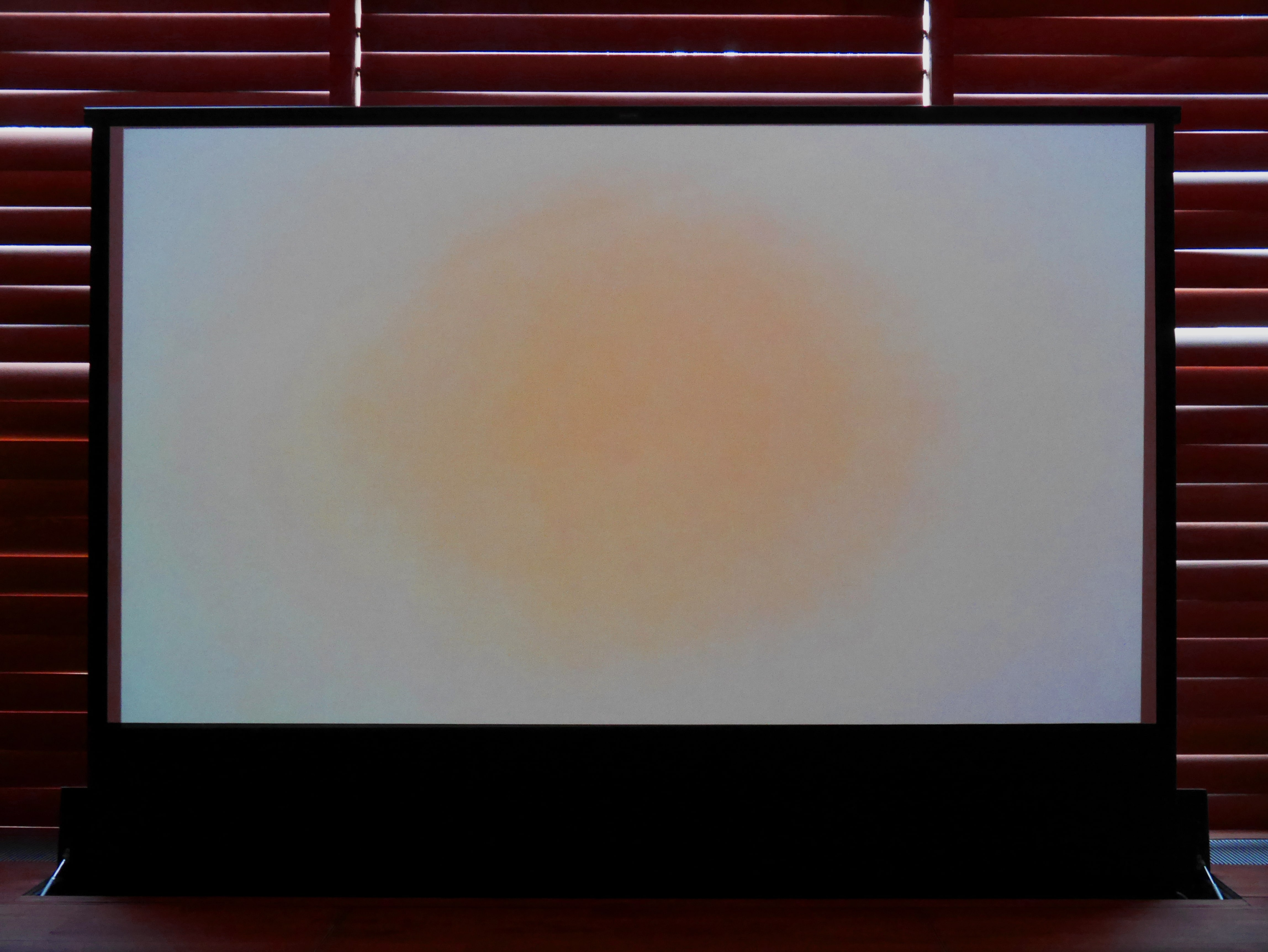 Blush toned glow in central position projected onto large screen mounted from the floor