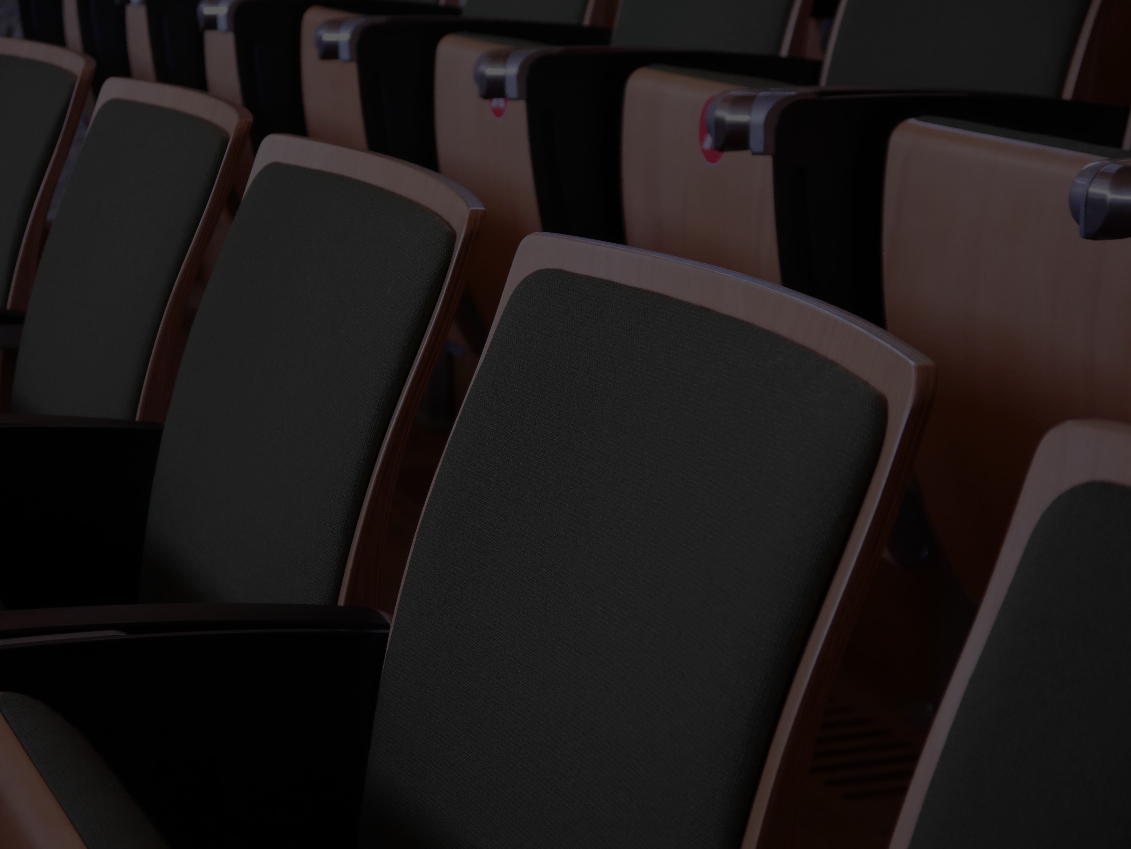Right positioned close up of empty audience seating, blush toned glow visible against the unoccupied rows