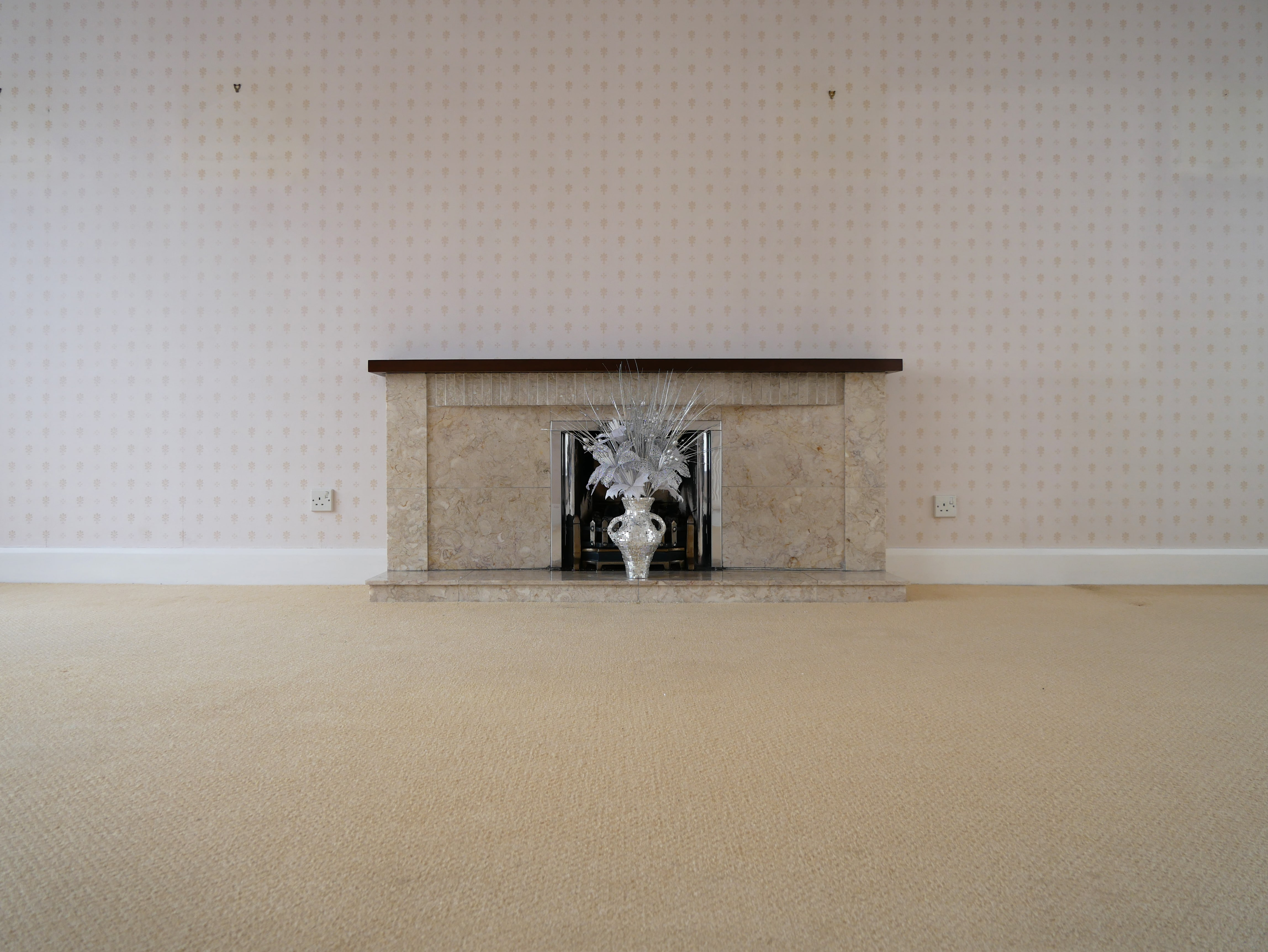 An installation shot of a vase with a mirrored surface, which holds an arrangement of artificial, glittery, silver and white flowers and sits on a mantelpiece.