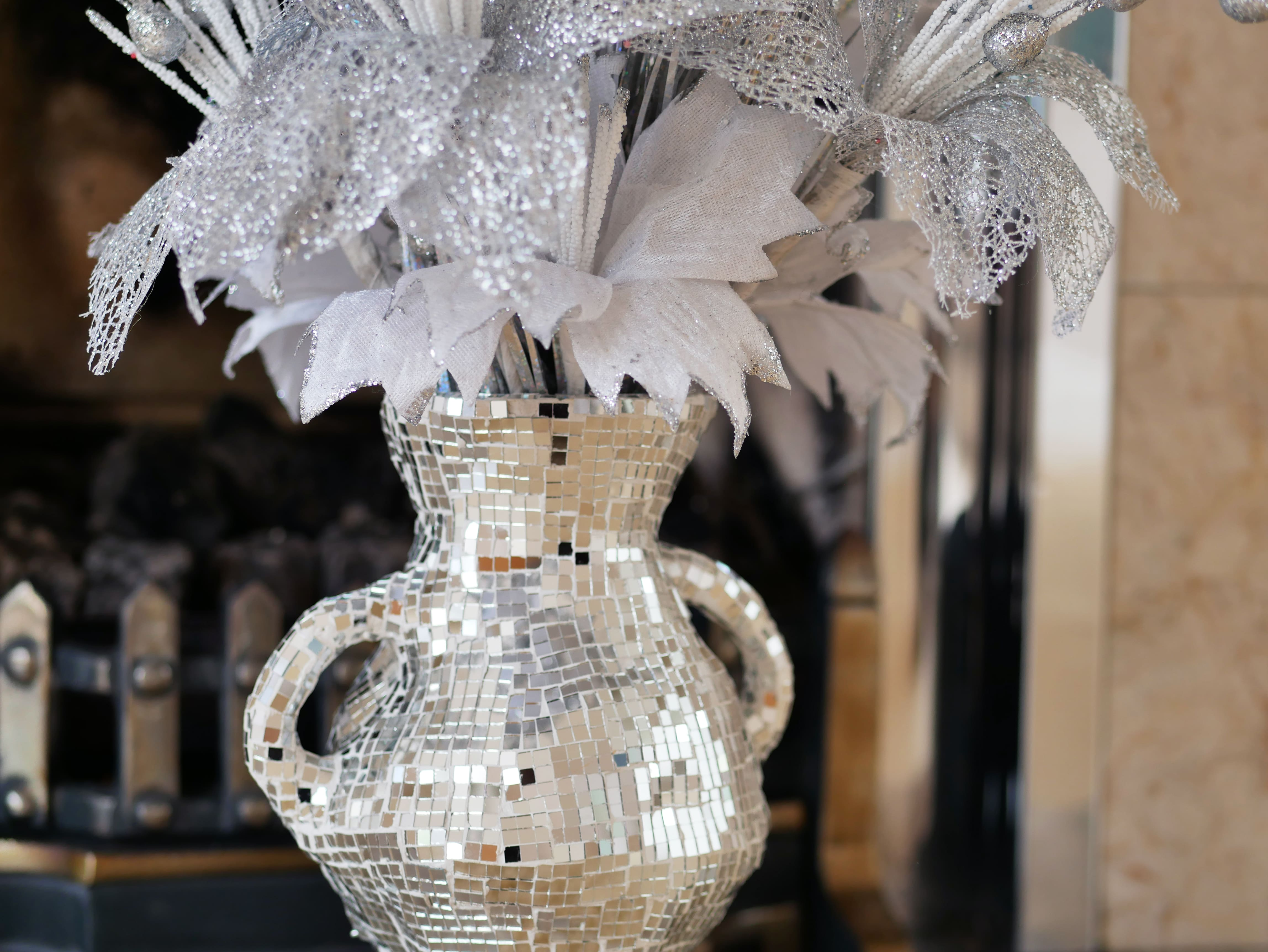 A detail shot of a vase with a mirrored surface, which holds an arrangement of artificial, glittery, silver and white flowers and sits on a mantelpiece.
