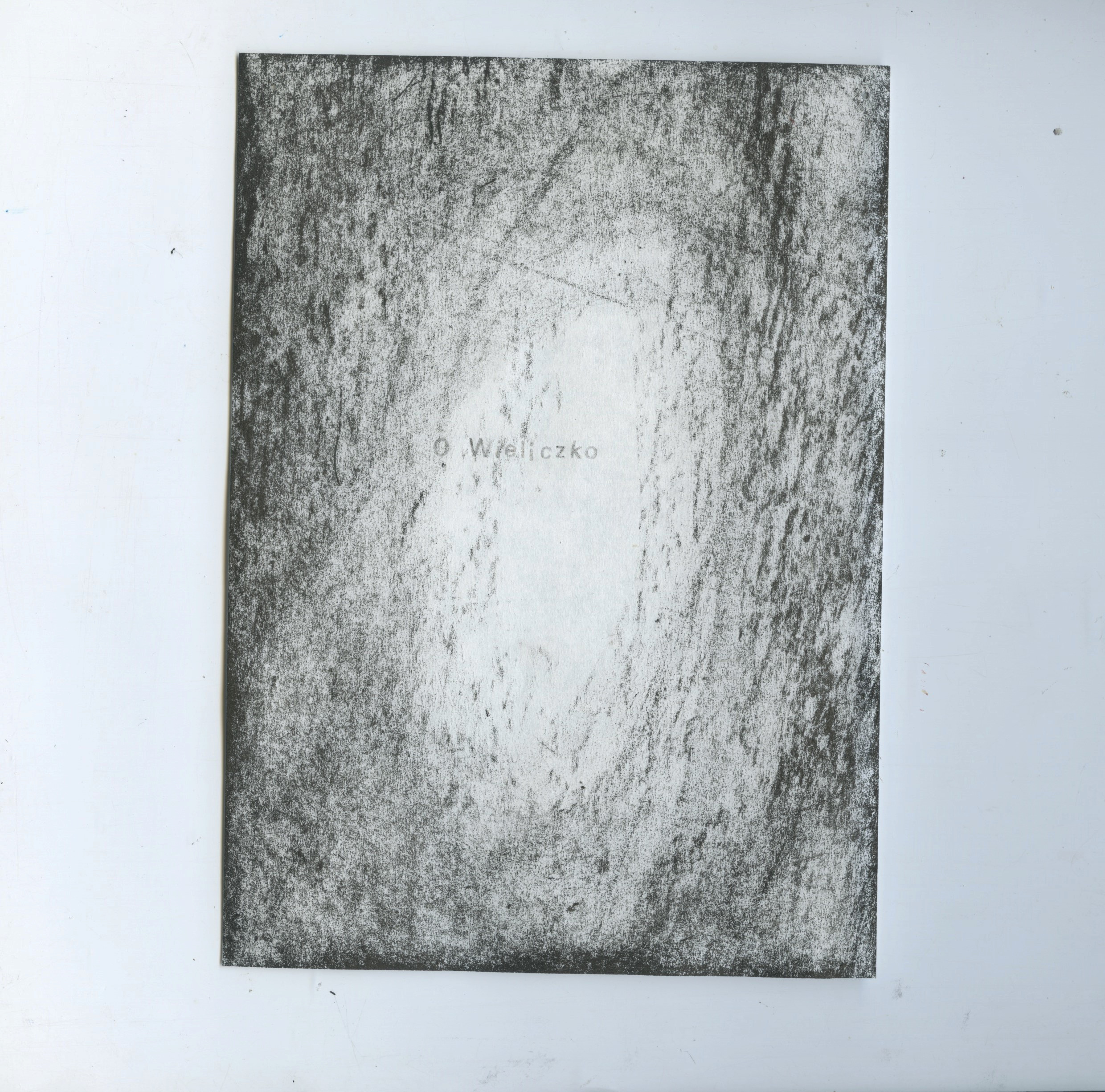"""Scanned sheet of Bible paper with text printed on it in silver ink. The text reads: """"O Wieliczko"""". There is a textured graphite vignette surrounding the text."""