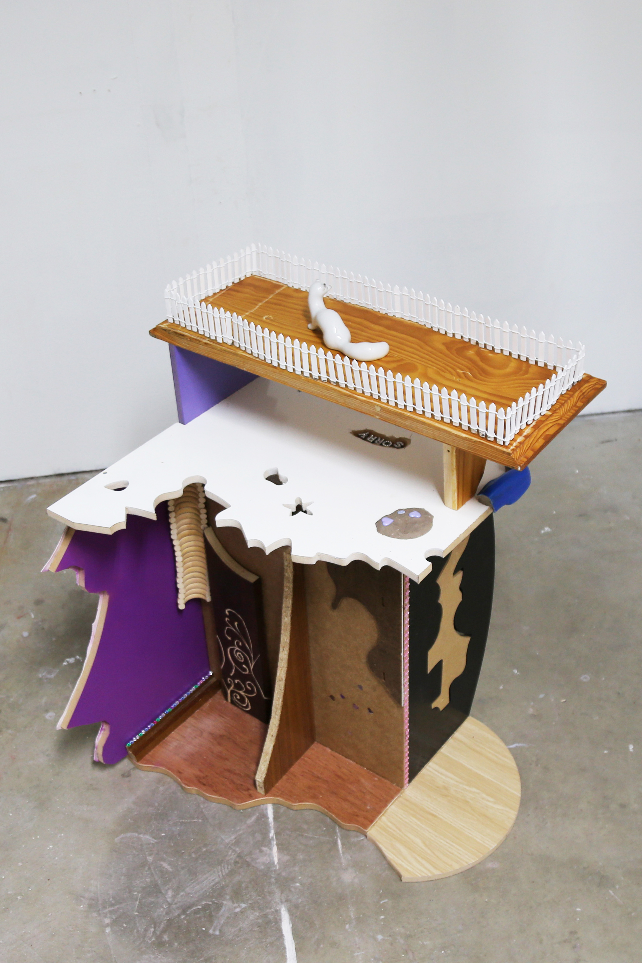 A white, purple, black and brown sculpture on a concrete floor, viewed from above