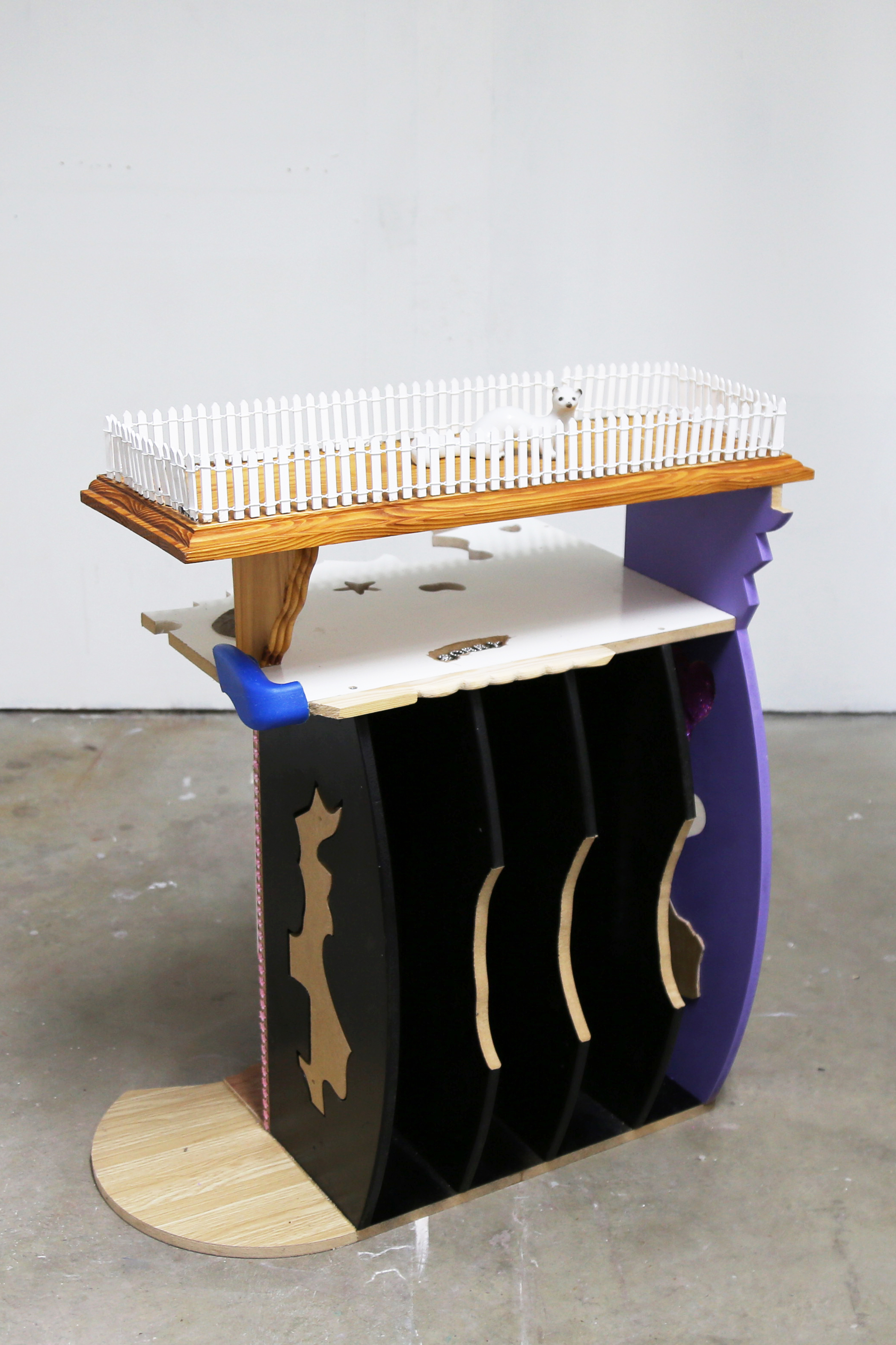 A white, purple, black and brown sculpture