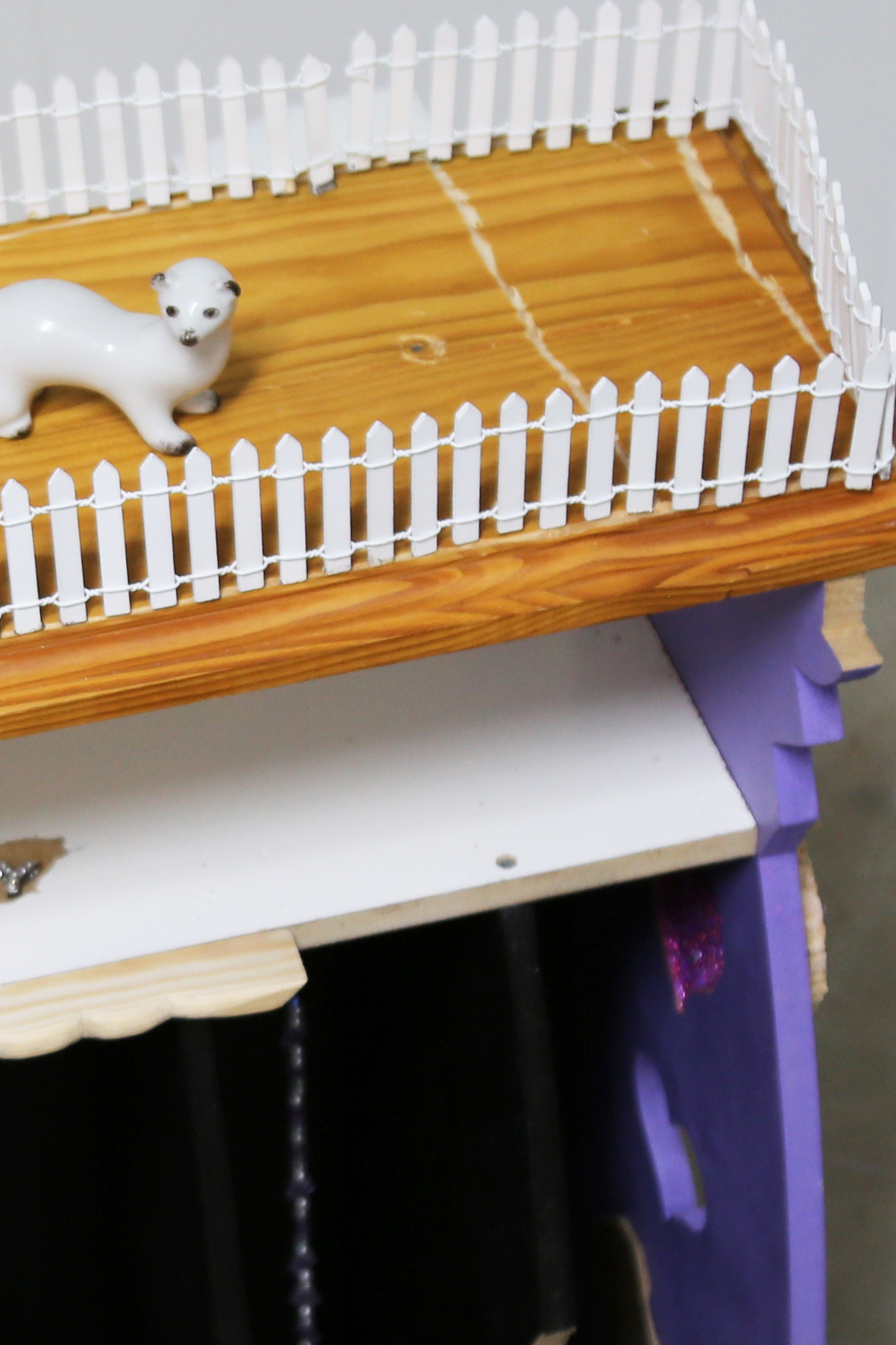 Detail of a white ceramic weasel figurine surrounded by a white model picket fence at the top of the sculpture