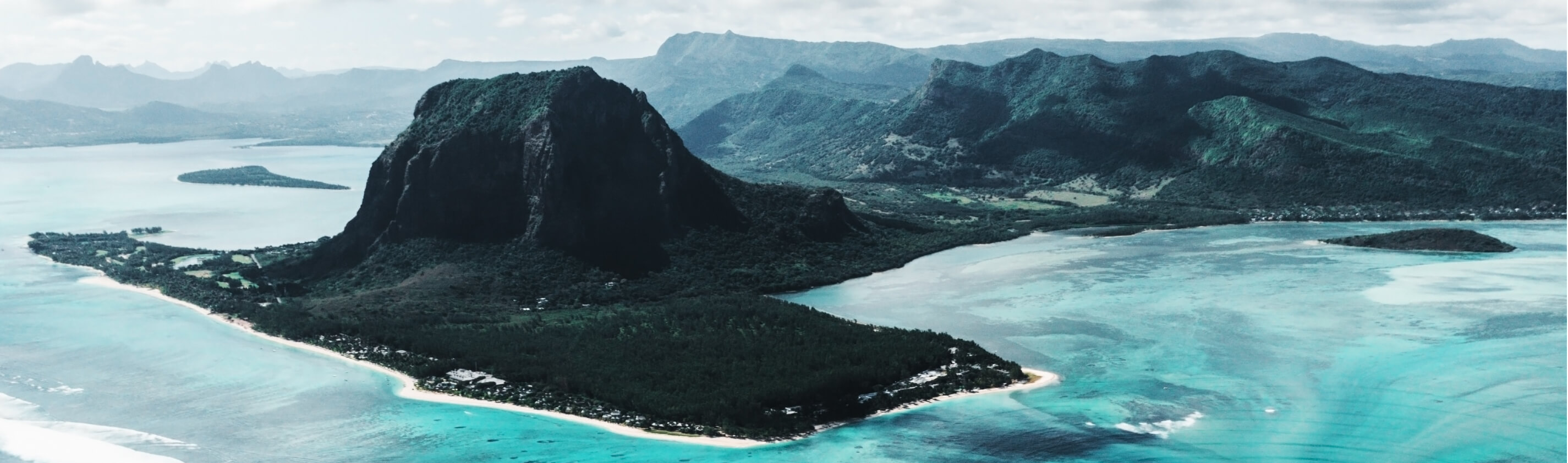 The turquoise waters of the Mauritius surround a small peninsula of land — jutting out from the low lying mainland, a densely covered mountain emerges.