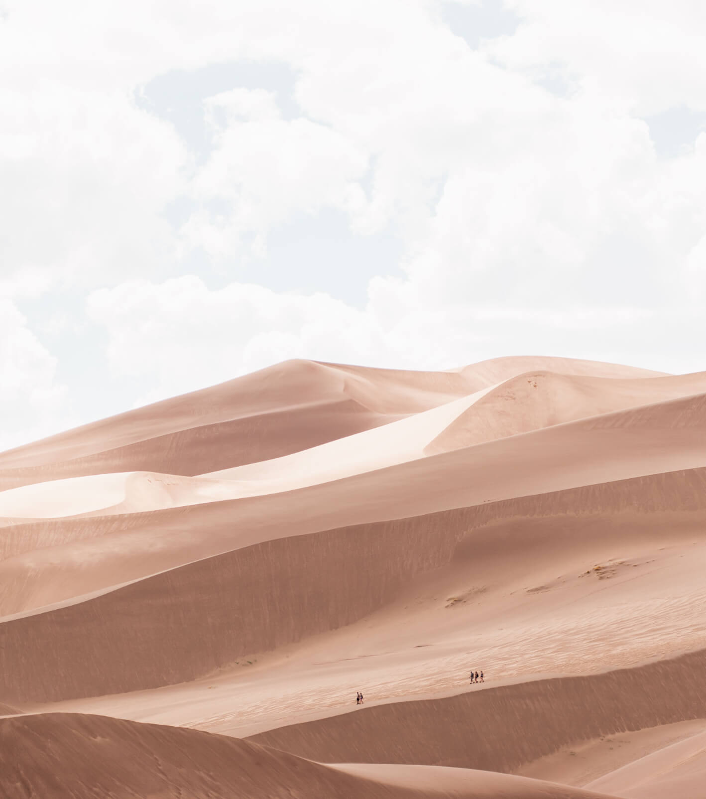 A hazy white sky with a blueish tint gives way to a sculptural section of desert sand dunes. On the horizon of the tallest dune you can make out the silhouette of 3 people.