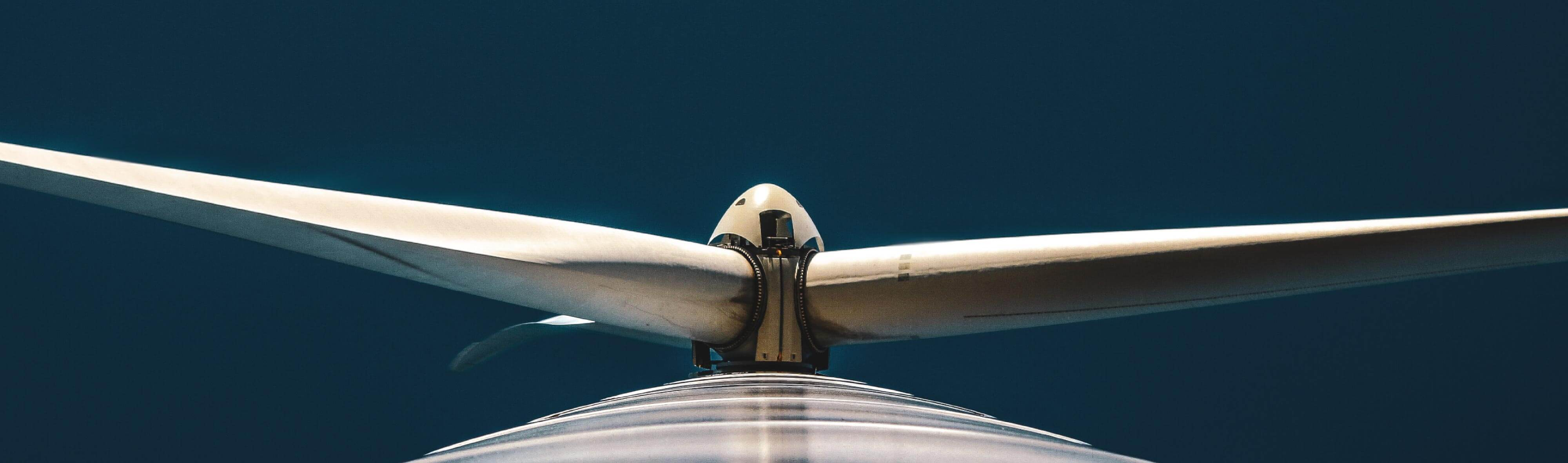 A dark blue sky acts as the background for this shot looking straight up at a wind turbine.