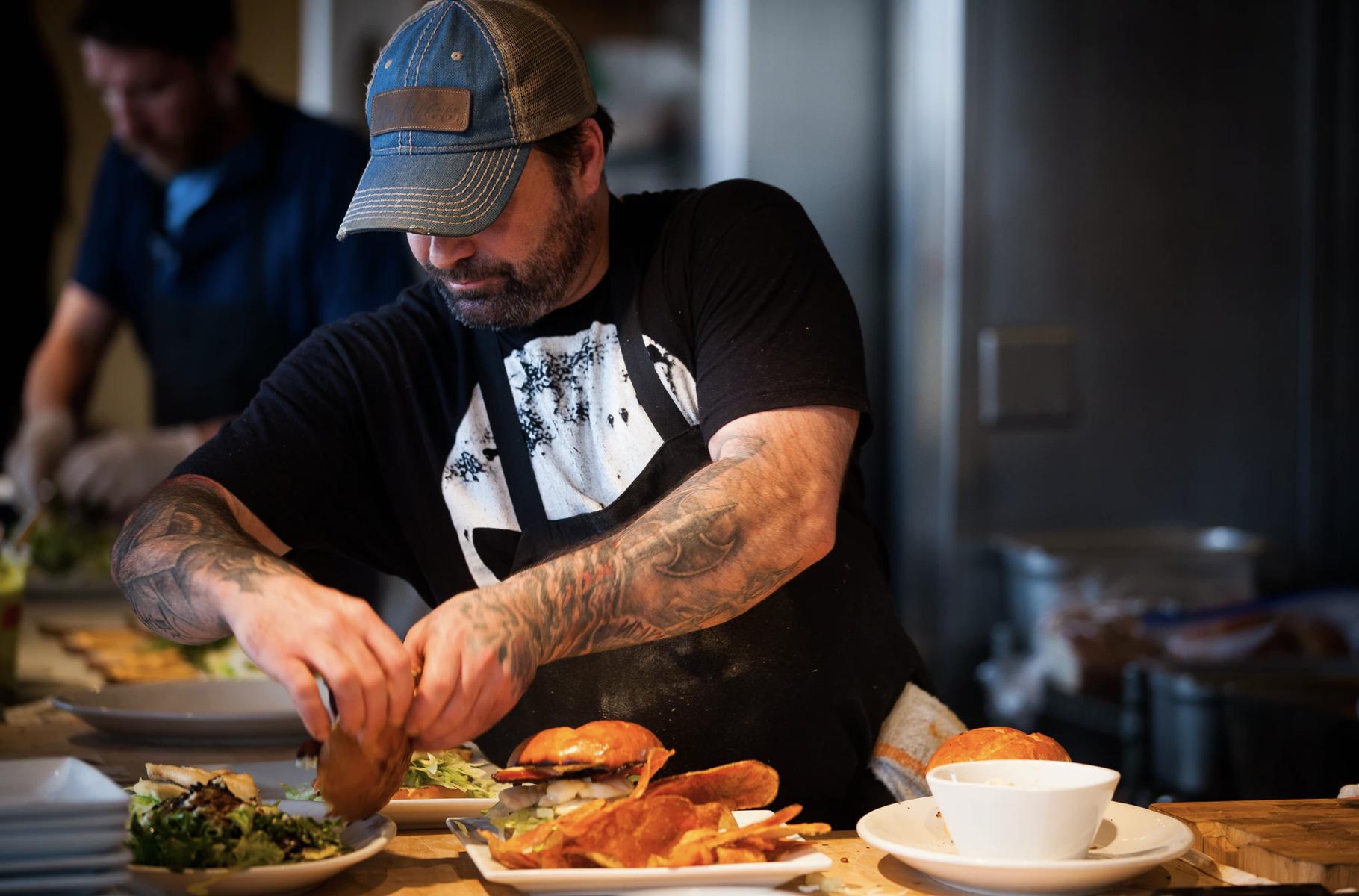 Een foto van een kok die hamburgers maakt. Uiteraard besteld via de Onesix Kiosk