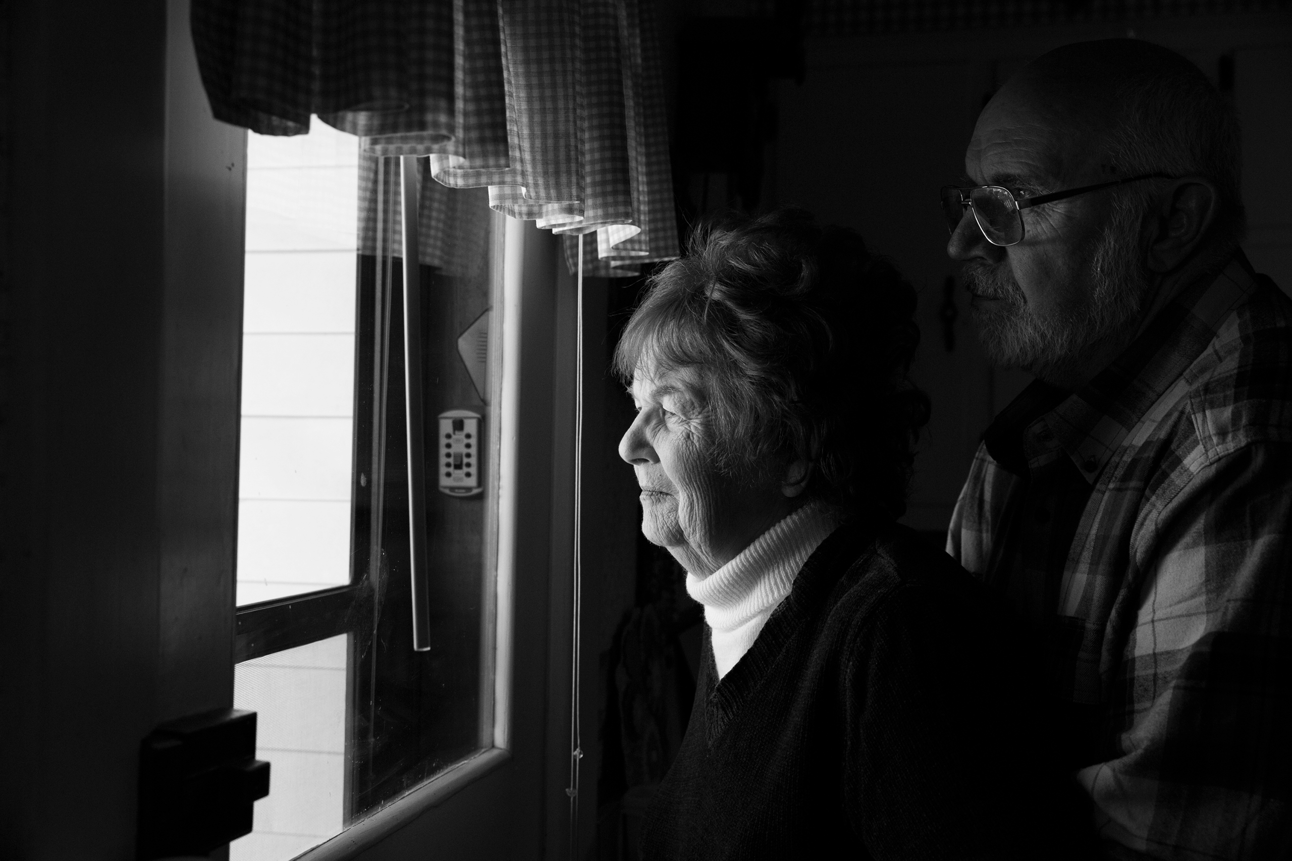 Senior couple Karen and Ed looking out a window