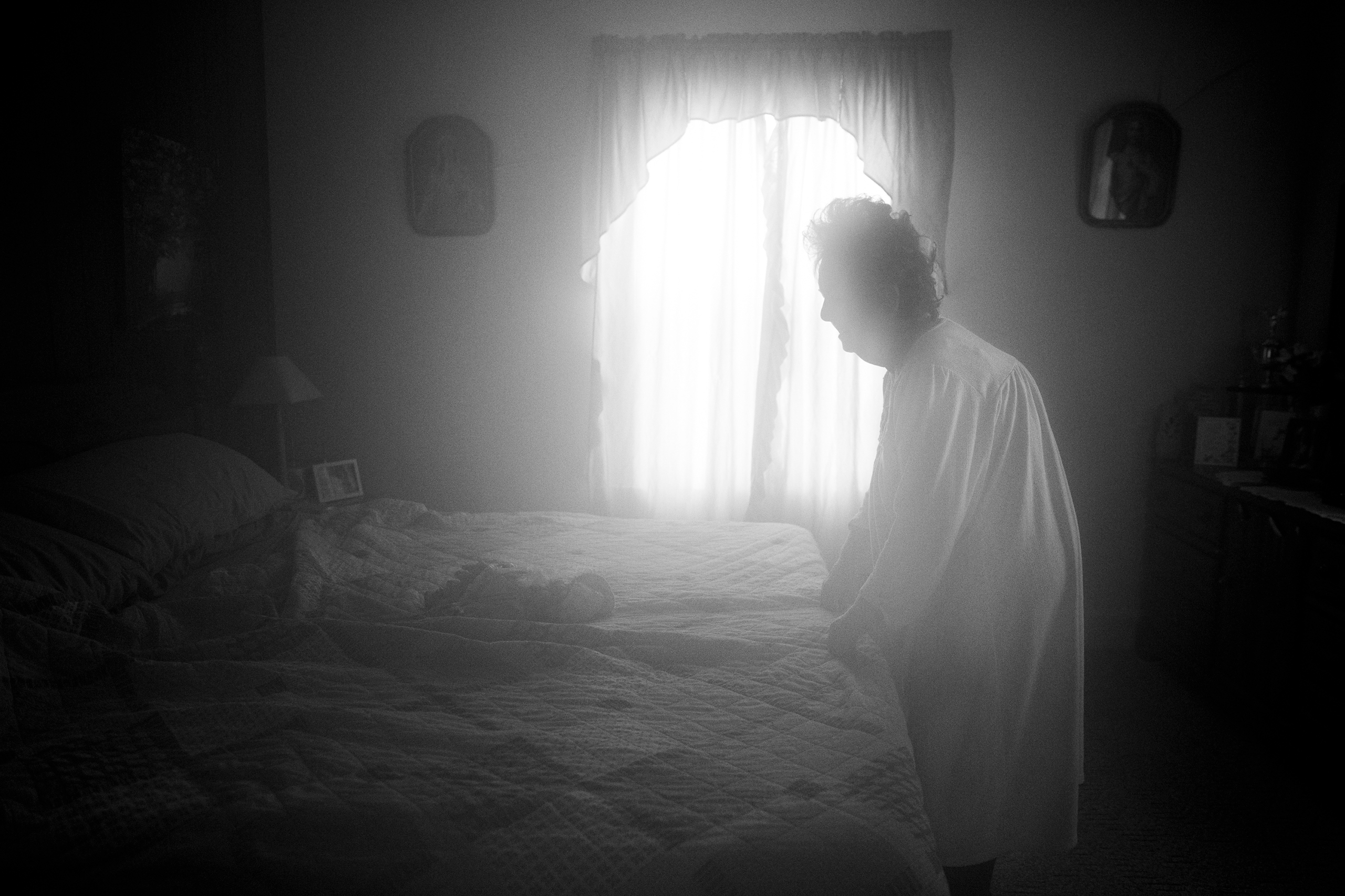 Karen stands at the end of her bed in a foggy room