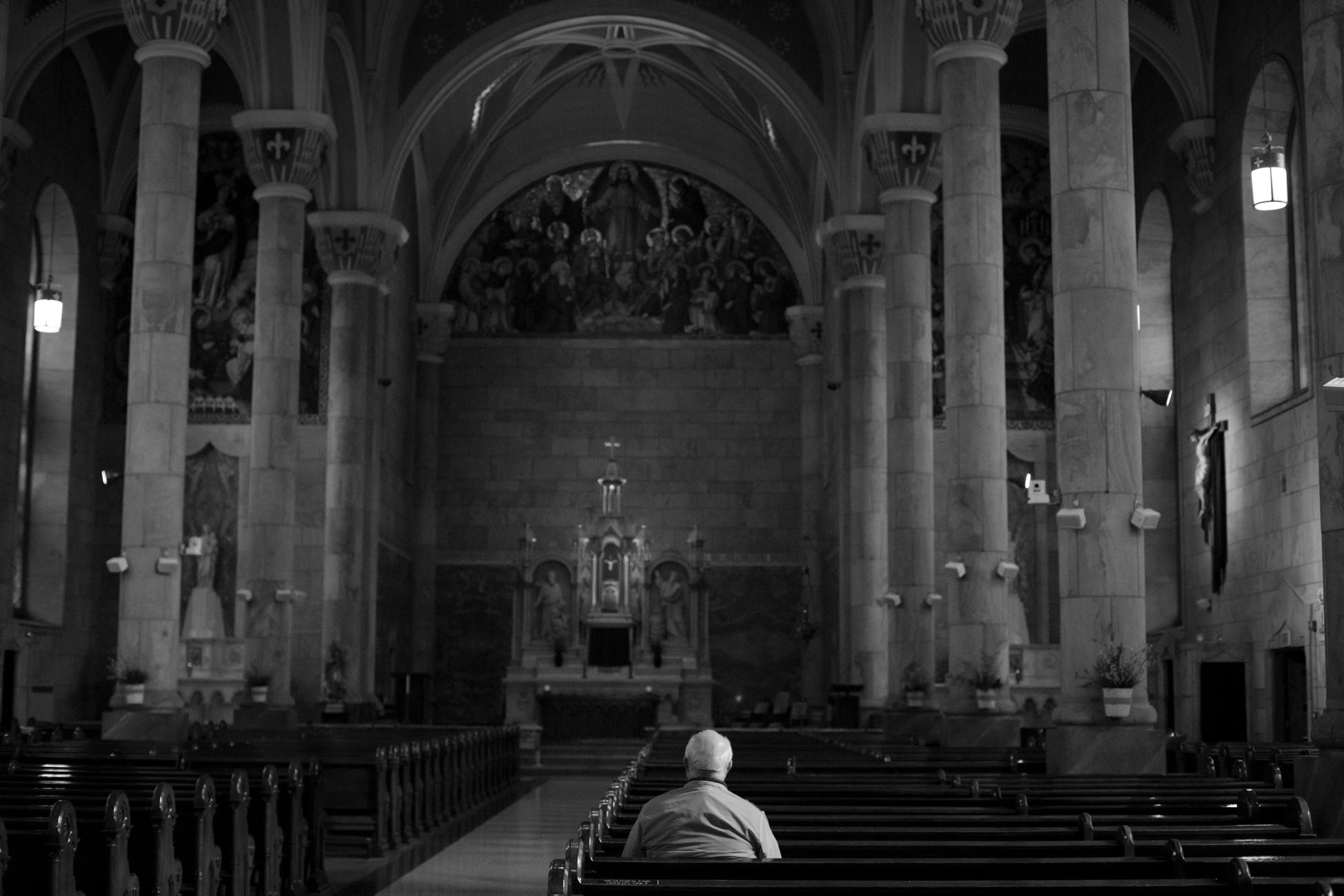 Ed prays in a empty Catholic church
