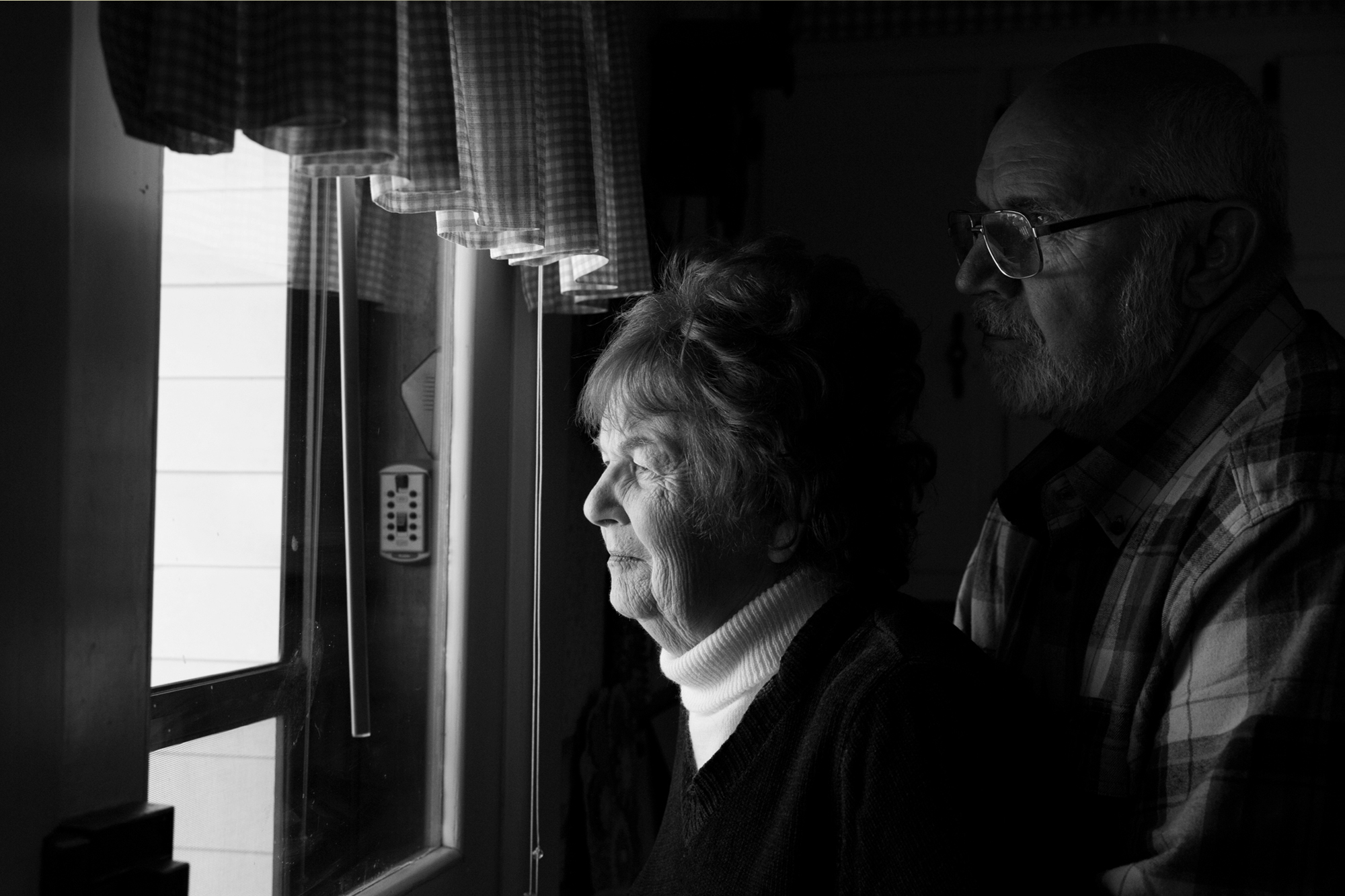 Senior couple looking out window, yellow border, links to Love Is Not A Memory