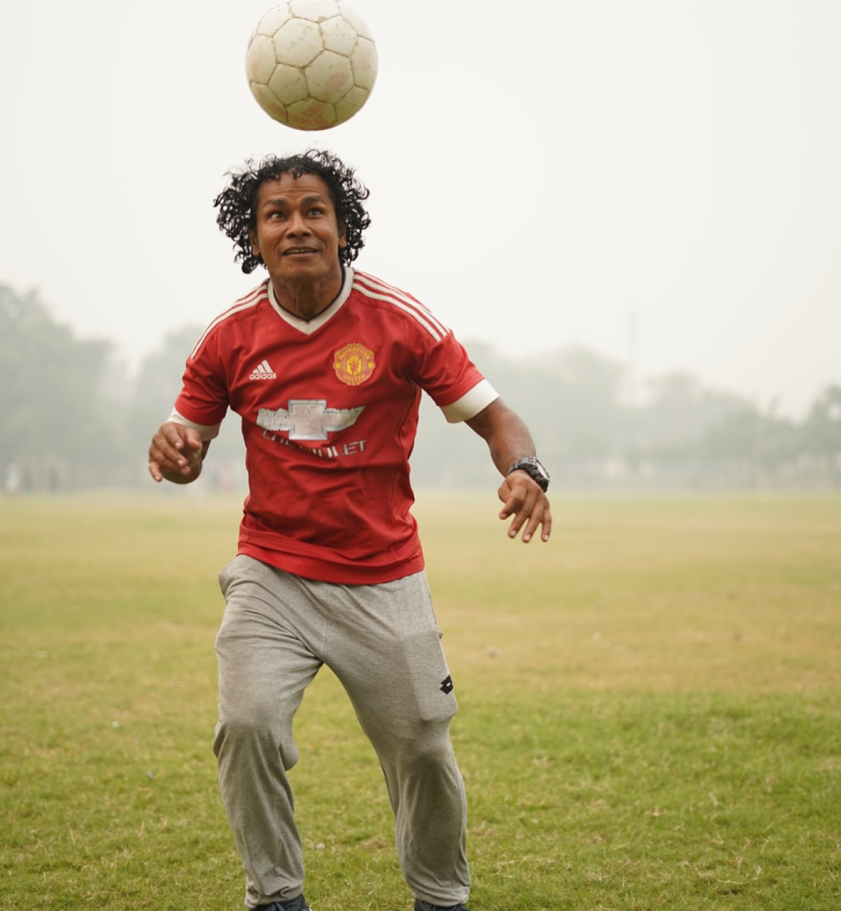 Boy playing football (soccer) in a green field