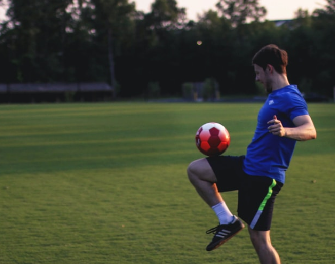 Young adult man playing football
